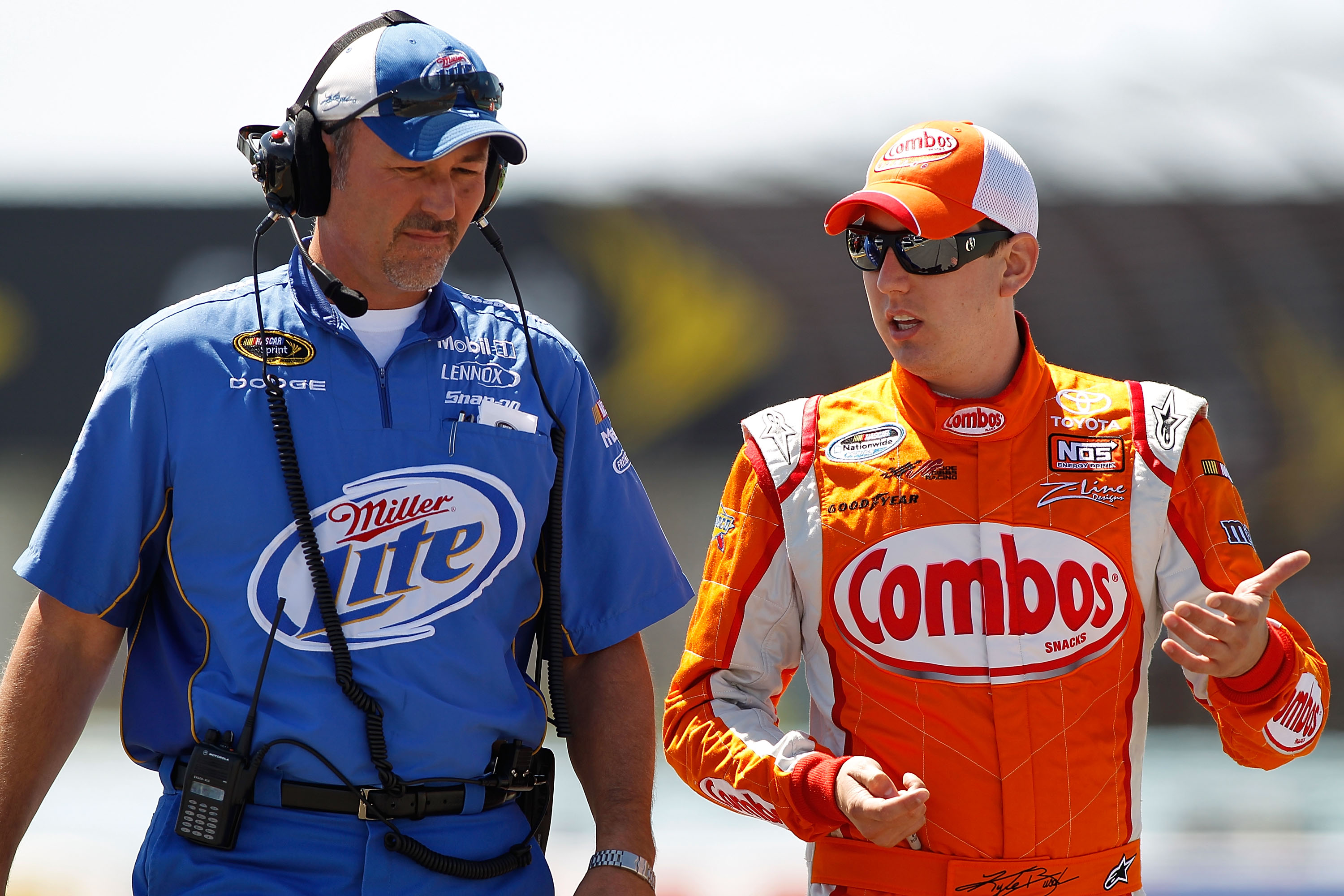 WATKINS GLEN, NY - AUGUST 07:  Kyle Busch (R), driver of the #18 M&M's Toyota, talks with Steve Addington (L), crew chief of the #2 Miller Lite Dodge, during qualifying for the NASCAR Sprint Cup Series Heluva Good! Sour Cream Dips at Watkins Glen Internat