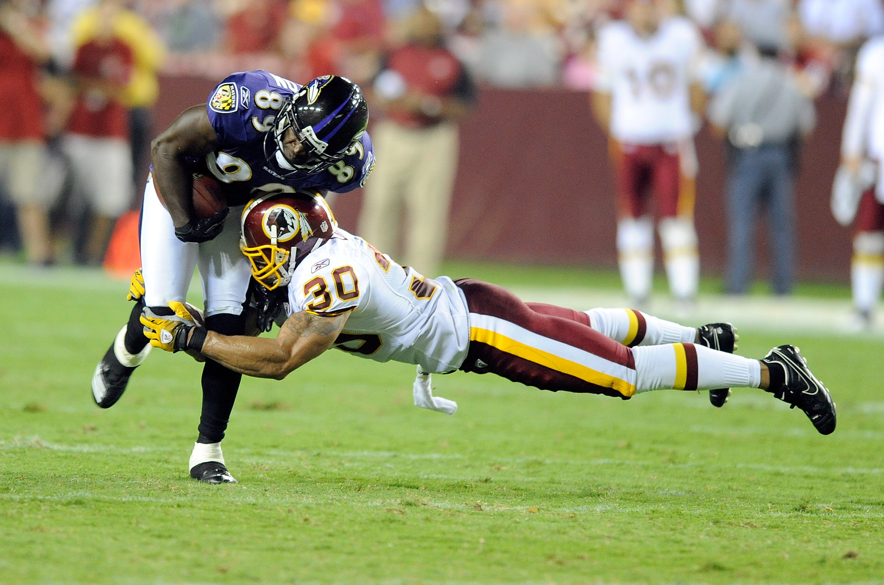 LANDOVER, MD - AUGUST 21:  Mark Clayton #89 of the Baltimore Ravens is tackled during the preseason game by LaRon Landry #30 of the Washington Redskins at FedExField on August 21, 2010 in Landover, Maryland.  (Photo by Greg Fiume/Getty Images)
