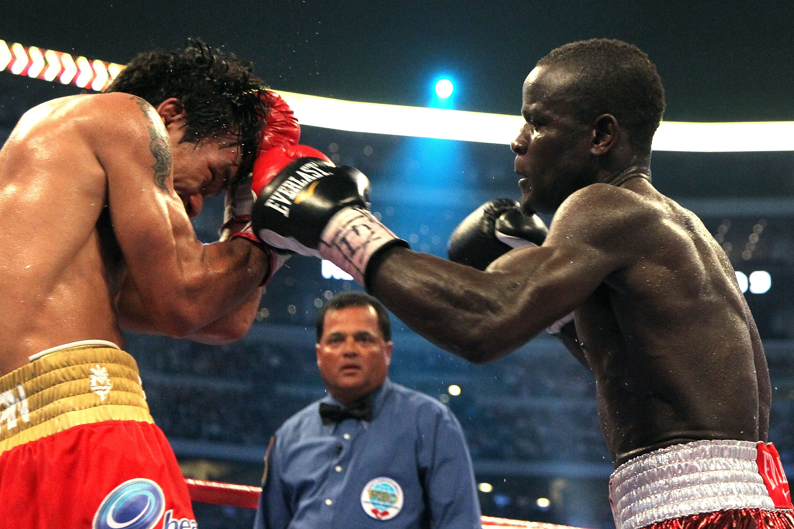 ARLINGTON, TX - MARCH 13:  (R-L) Joshua Clottey of Ghana throws a left to the face of Manny Pacquiao of the Philippines during the WBO welterweight title fight at Cowboys Stadium on March 13, 2010 in Arlington, Texas.  (Photo by Jed Jacobsohn/Getty Images