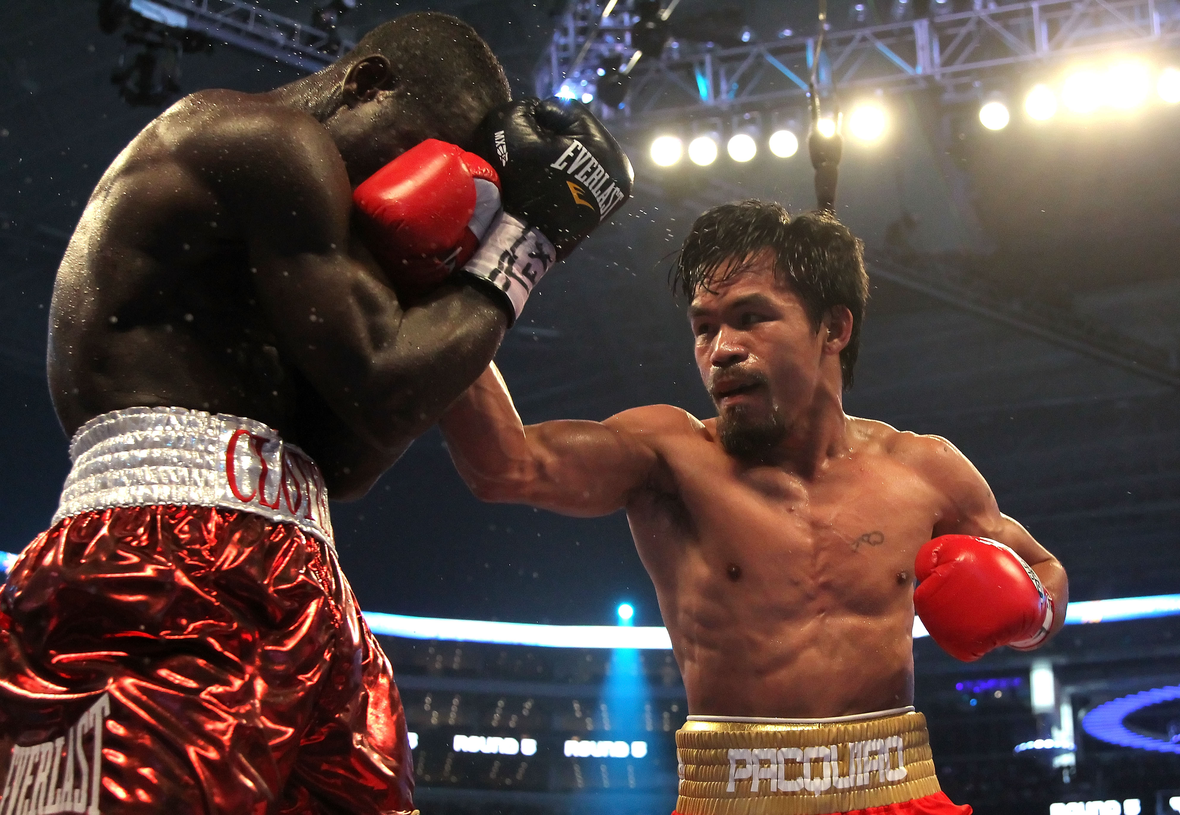 ARLINGTON, TX - MARCH 13:  (R-L) Manny Pacquiao of the Philippines throws a right to the head of Joshua Clottey of Ghana during the WBO welterweight title fight at Cowboys Stadium on March 13, 2010 in Arlington, Texas.  (Photo by Jed Jacobsohn/Getty Image