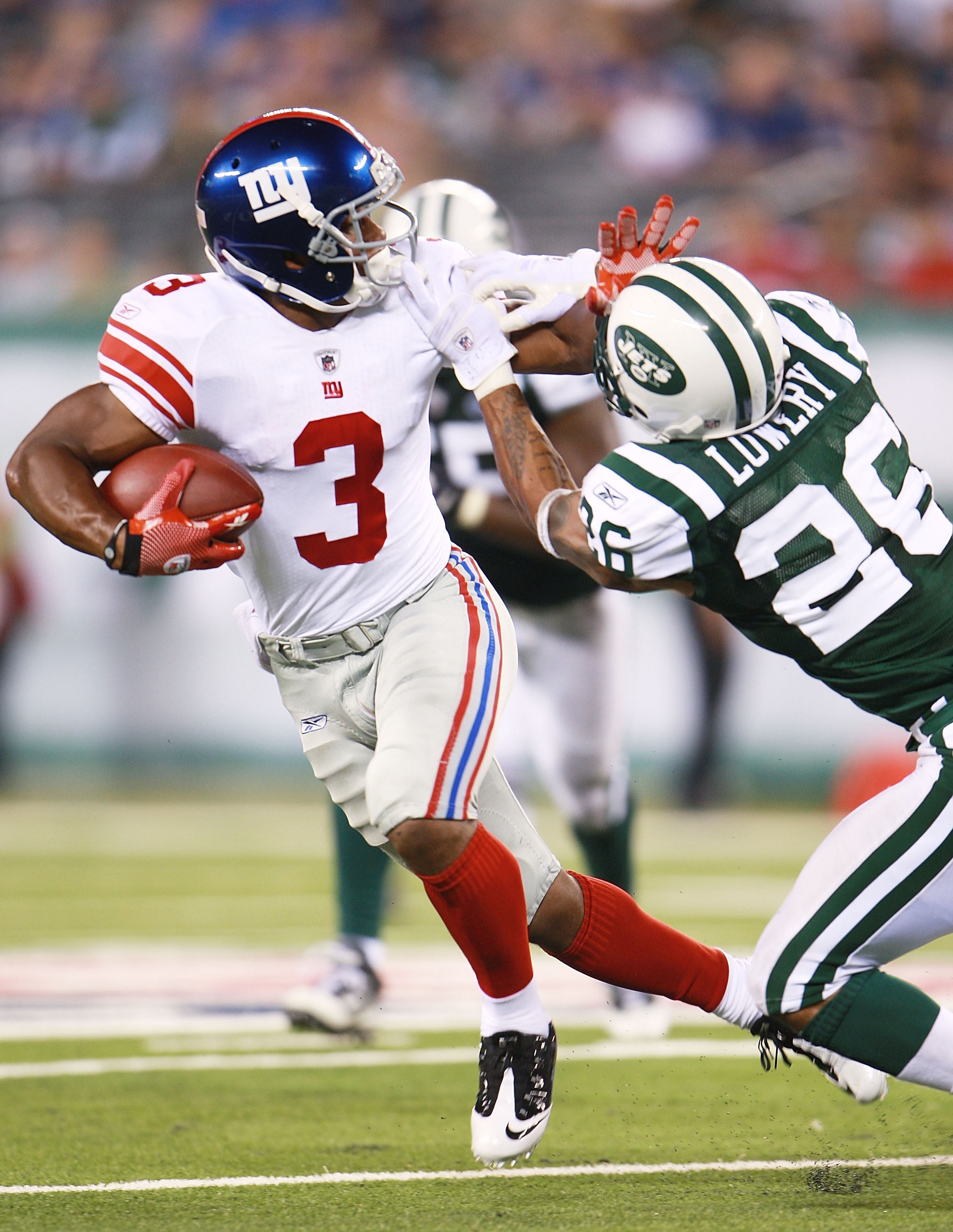 EAST RUTHERFORD, NJ - AUGUST 16:  Victor Cruz #3 of the New York Giants breaks a tackle from Dwight Lowery #26 of the New York Jets during the preseason game at New Meadowlands Stadium on August 16, 2010 in East Rutherford, New Jersey. The  Giants won 31