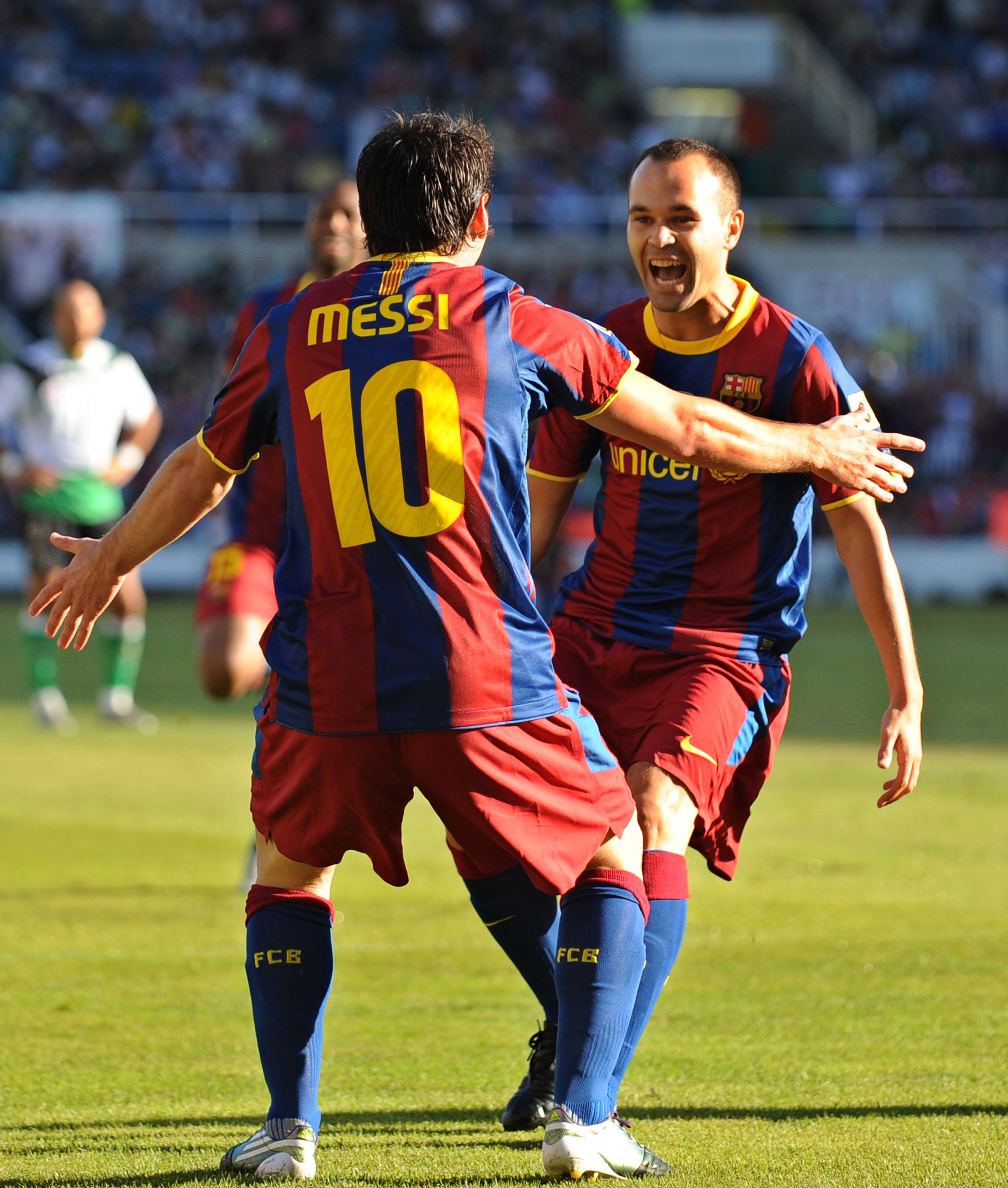 SANTANDER, SPAIN - AUGUST 29:  Leo Messi of Barcelona celebrates with Andres Iniesta (R) after scoring Barcelona's first goal during the La Liga match between Racing Santander and Barcelona at El Sardinero stadium on August 29, 2010 in Santander, Spain.