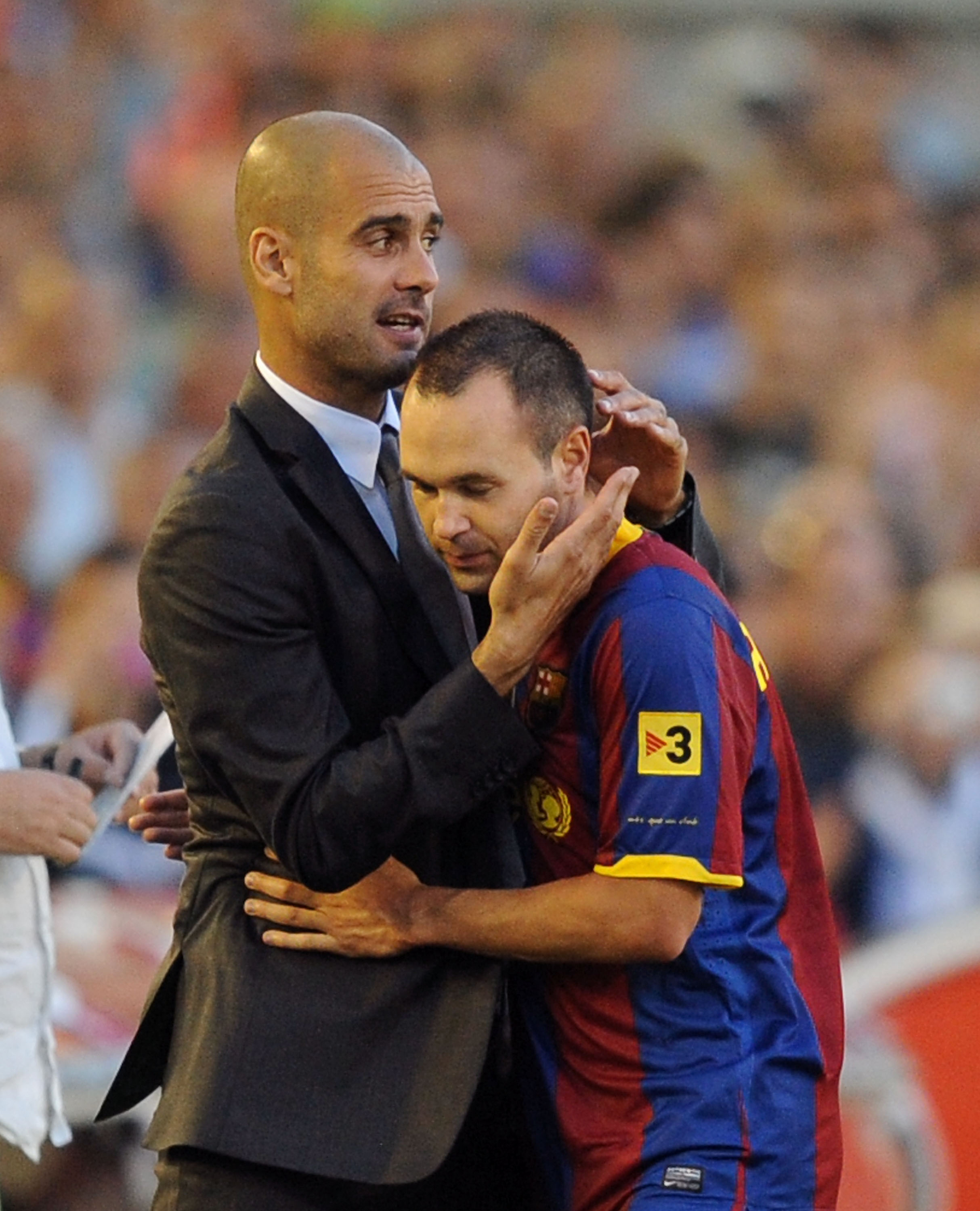 SANTANDER, SPAIN - AUGUST 29:  Barcelona manager Josep Guardiola (L) embraces Andres Iniesta after he was substituted during the La Liga match between Racing Santander and Barcelona at El Sardinero stadium on August 29, 2010 in Santander, Spain.  (Photo b