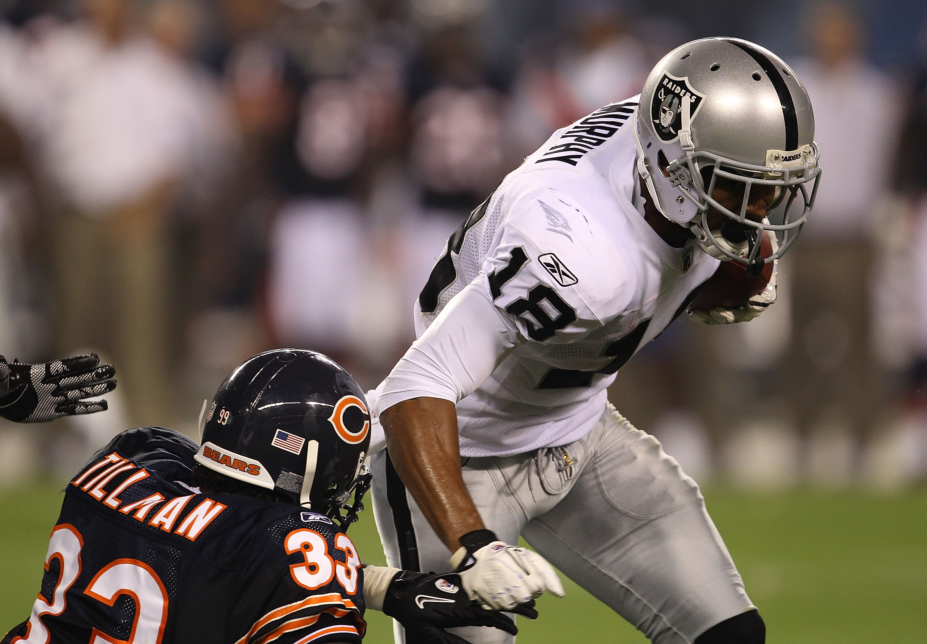 CHICAGO - AUGUST 21: Louis Murphy #18 of the Oakland Raiders runs for yardage as Charles Tillman #33 of the Chicago Bears closes in during a preseason game at Soldier Field on August 21, 2010 in Chicago, Illinois. The Raiders defeated the Bears 32-17. (Ph