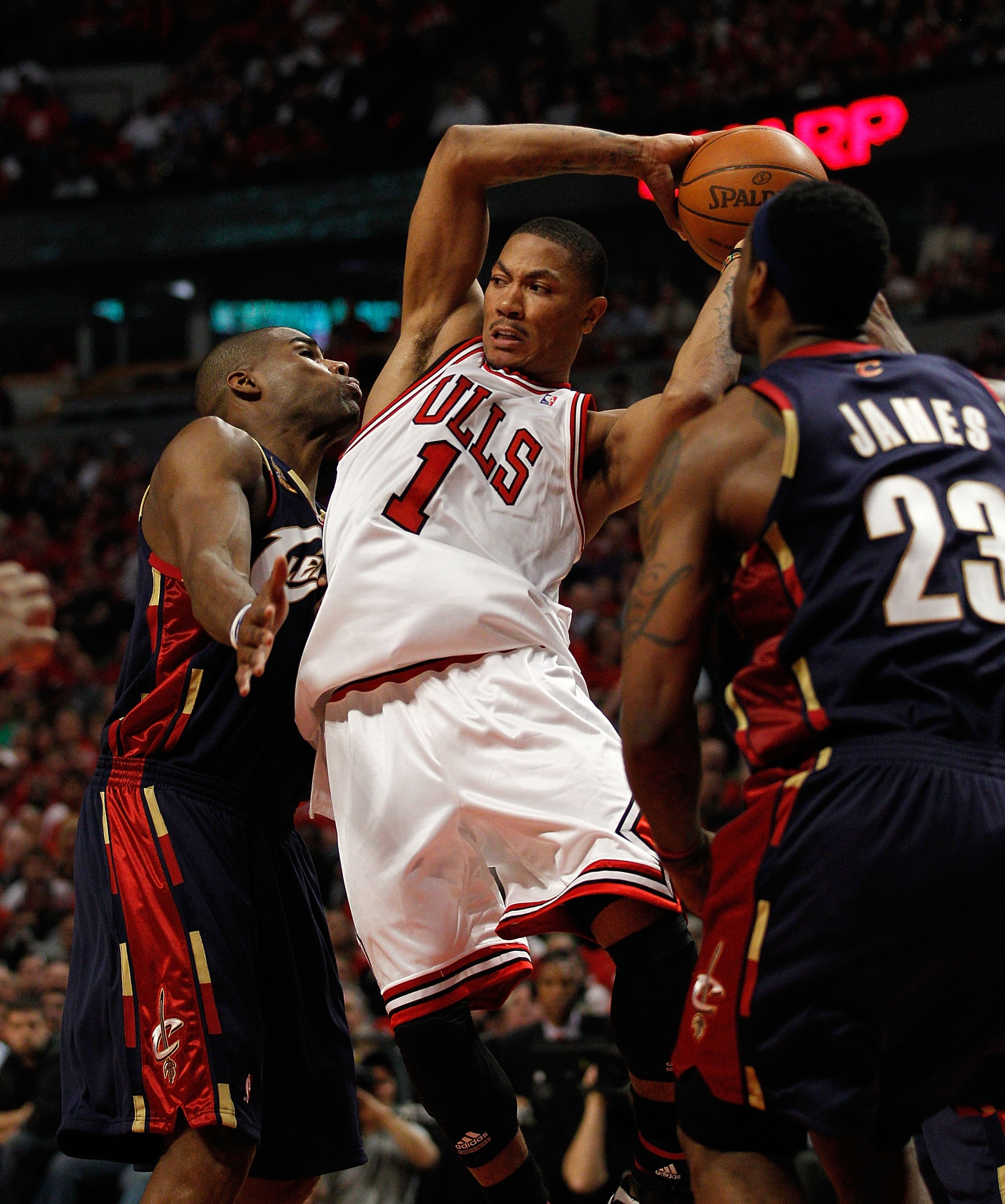 CHICAGO - APRIL 22: Derrick Rose #1 of the Chicago Bulls passes the ball between Antawn Jamison #4 and LeBron James #23 of the Cleveland Cavaliers in Game Three of the Eastern Conference Quarterfinals during the 2010 NBA Playoffs at the United Center on A
