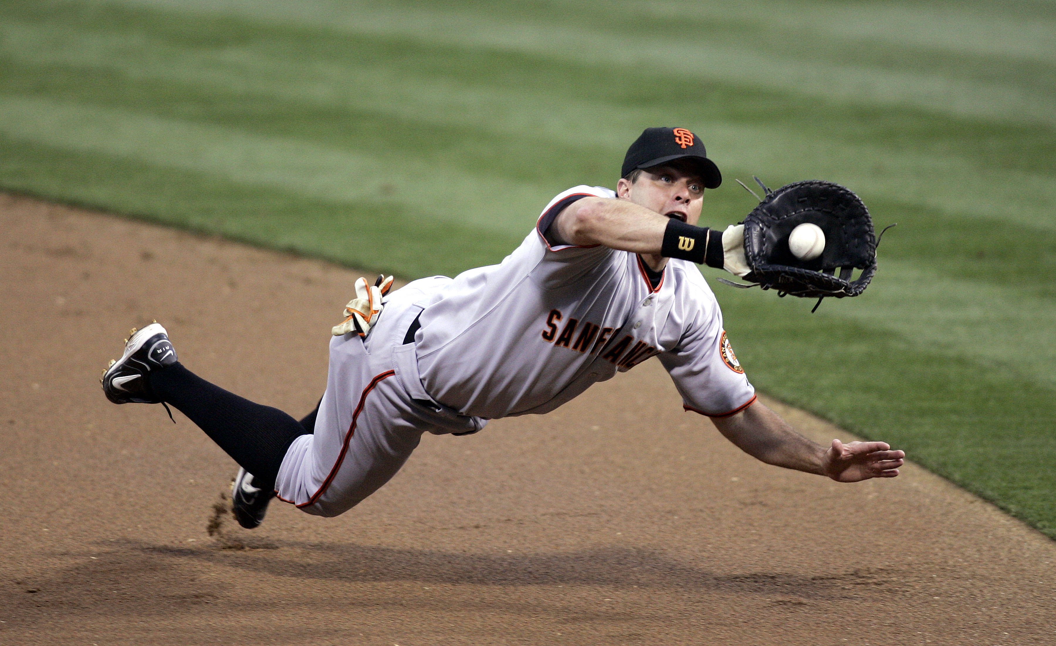 SAN DIEGO - JULY 1:  First baseman J.T. Snow #6 of the San Francisco Giants tries to catch a line drive hit by Xavier Nady #22 of the San Diego Padres in the first inning on July 1, 2005 at PETCO Park in San Diego, California.  (Photo by Donald Miralle/Ge