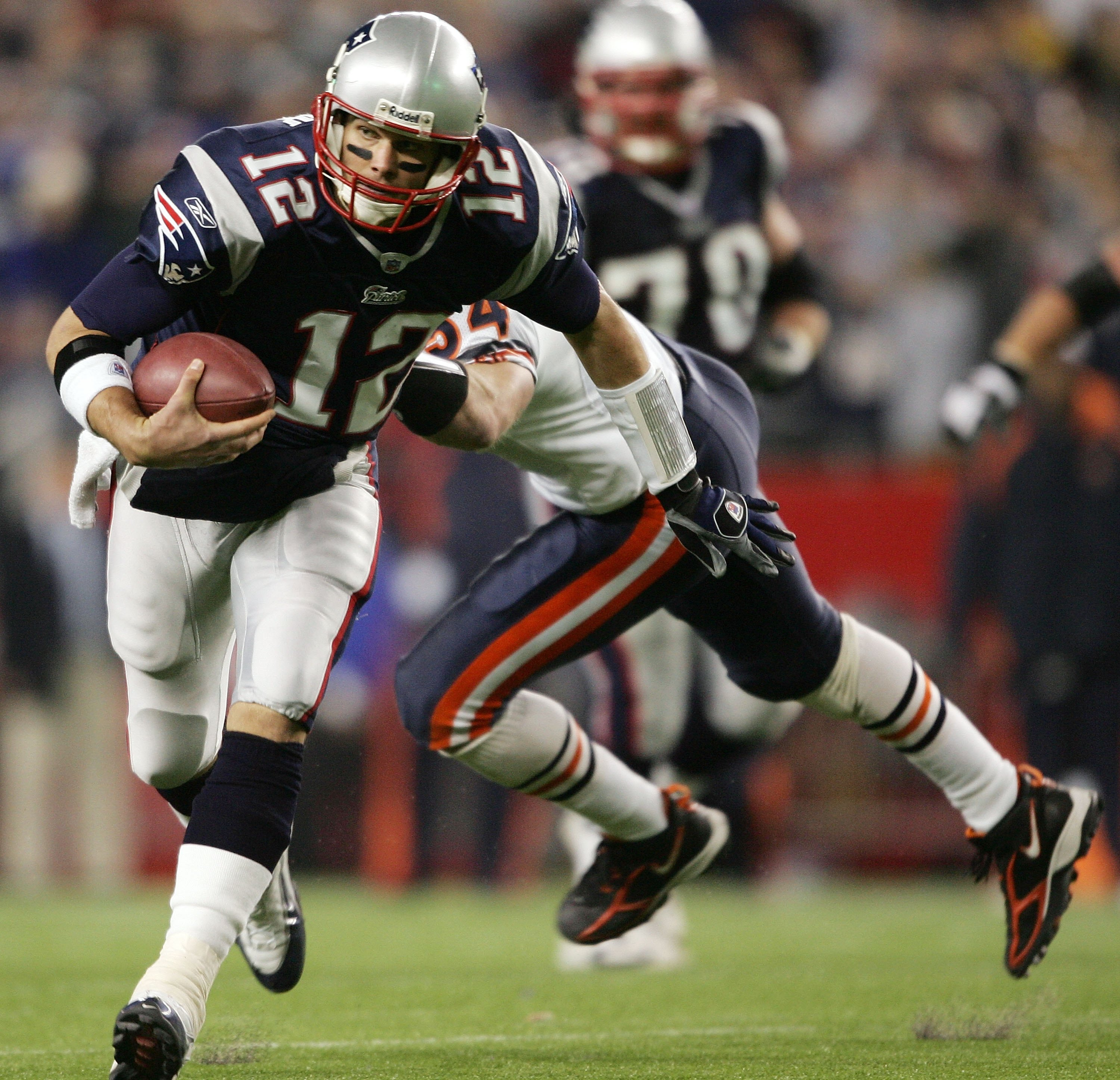 FOXBORO, MA - NOVEMBER 26:  Tom Brady #12 of the New England Patriots slips past Brian Urlacher #54 of the Chicago Bears to get the first down on November 26, 2006 at Gillette Stadium in Foxboro, Massachusetts. The New England Patriots defeated the Chicag