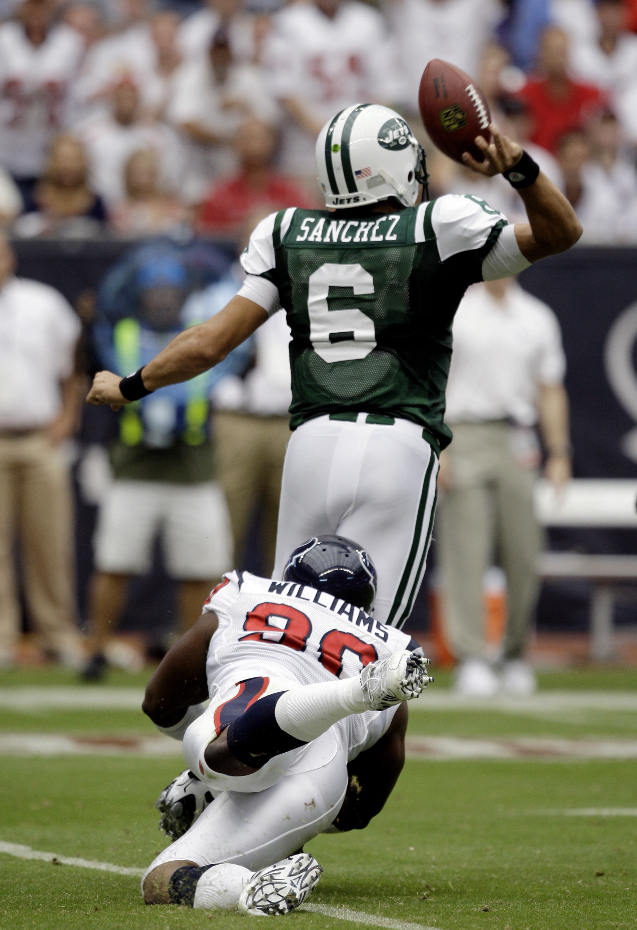 HOUSTON - SEPTEMBER 13: Quarterback Mark Sanchez #6 of the New York Jets is tackled from behind by defensive end Mario Williams #90 of the Houston Texans as he releases the ball at Reliant Stadium on September 13, 2009 in Houston, Texas.  (Photo by Bob Le