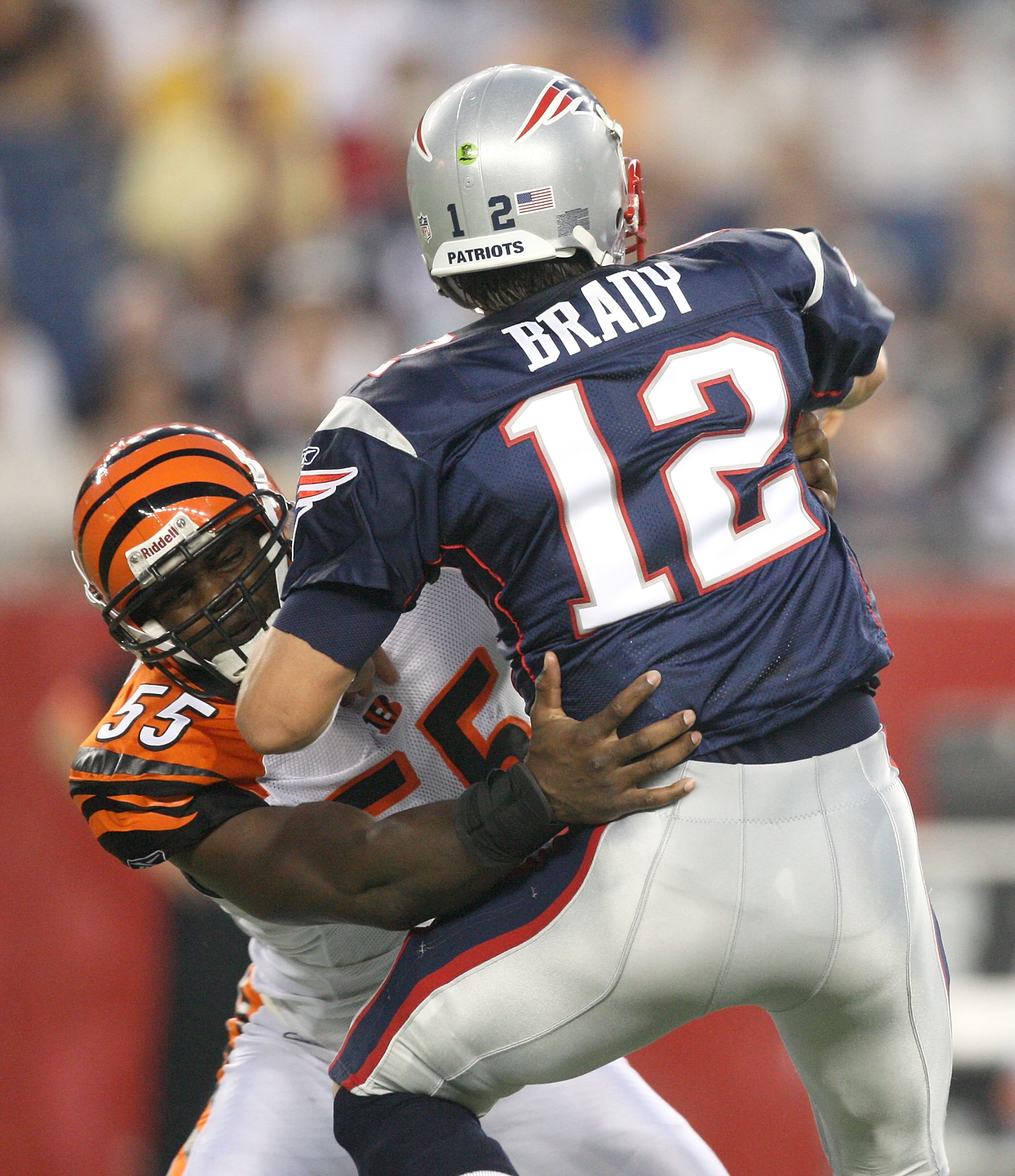 FOXBORO, MA - AUGUST 20:  Tom Brady #12 of the New England Patriots feels the pressure of Keith Rivers #55 of the Cincinnati Bengals at Gillette Stadium on August 20, 2009 in Foxboro, Massachusetts. (Photo by Jim Rogash/Getty Images)