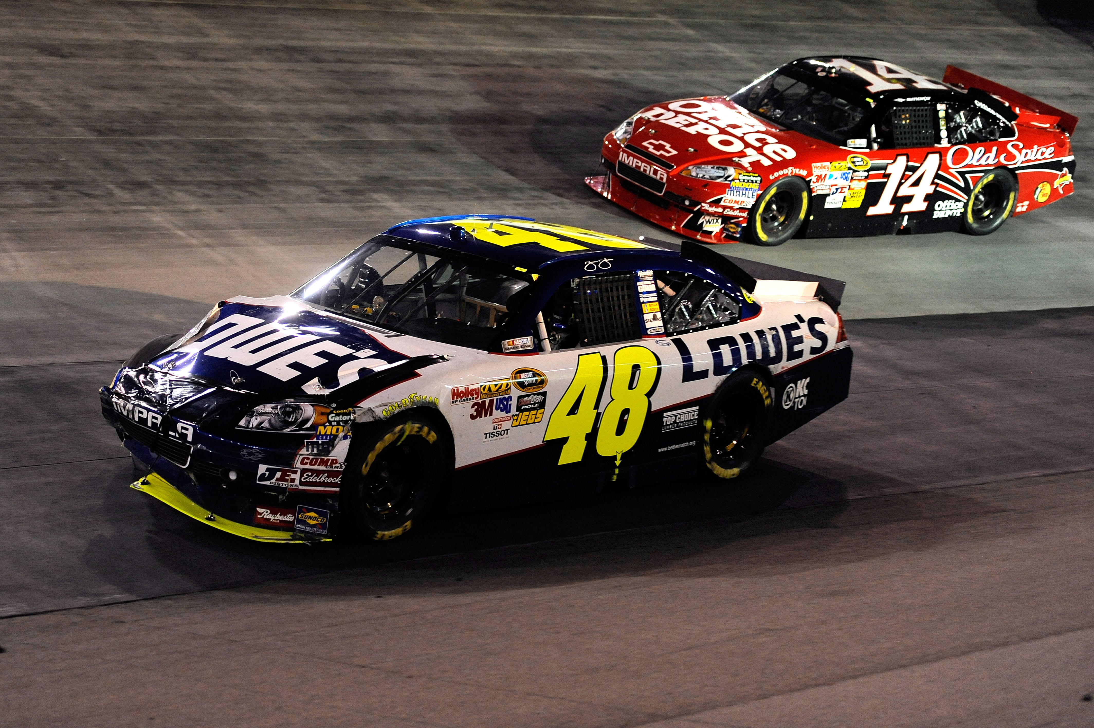 BRISTOL, TN - AUGUST 21:  Jimmie Johnson drives the #48 Lowe's Chevrolet down the aprin ahead of Tony Stewart, driver of the #14 Office Depot/Old Spice Chevrolet, after an incident on track in the NASCAR Sprint Cup Series IRWIN Tools Night Race at Bristol