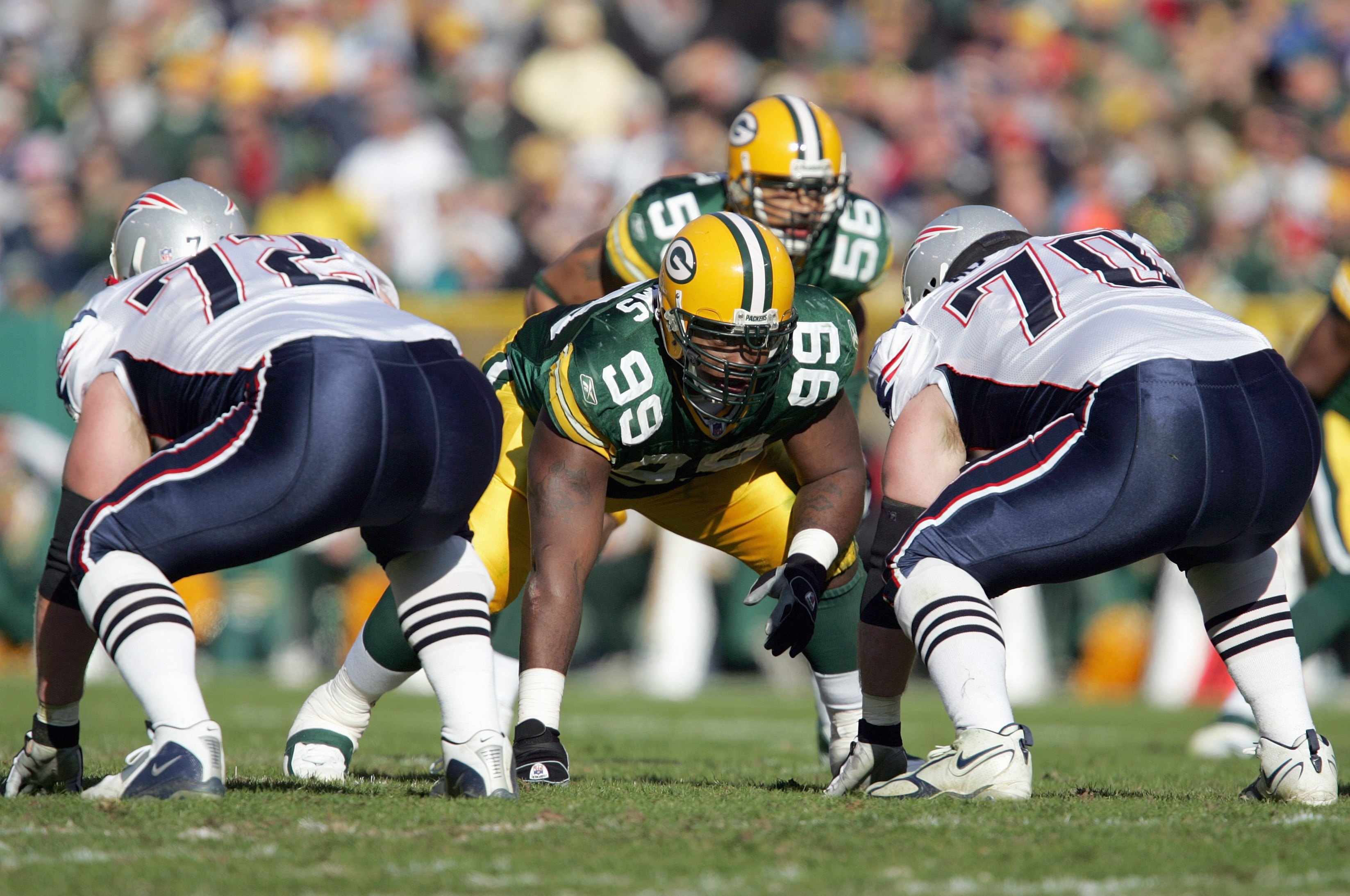 GREEN BAY, WI - NOVEMBER 19:  Corey Williams #99 of the Green Bay Packers gets ready on the line of scrimmage against Matt Light #72 and Logan Mankins #70 of the New England Patriots on November 19, 2006 at Lambeau Field in Green Bay, Wisconsin. The Patri