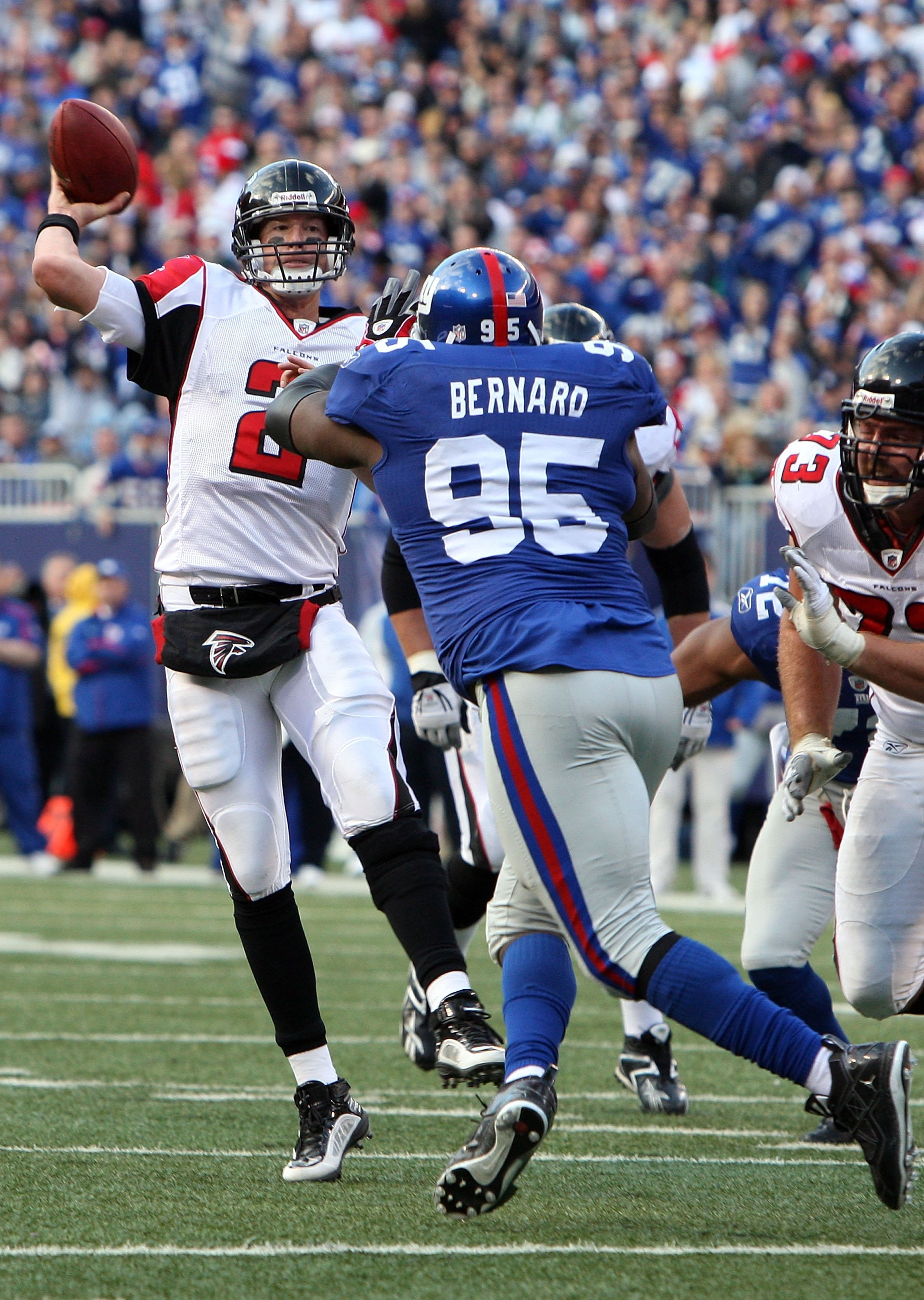 EAST RUTHERFORD, NJ - NOVEMBER 22:  Matt Ryan #2 of the Atlanta Falcons throws a pass under pressure from Rocky Bernard #95 of the New York Giants on November 22, 2009 at Giants Stadium in East Rutherford, New Jersey. The Giants defeated the Falcons 34-31