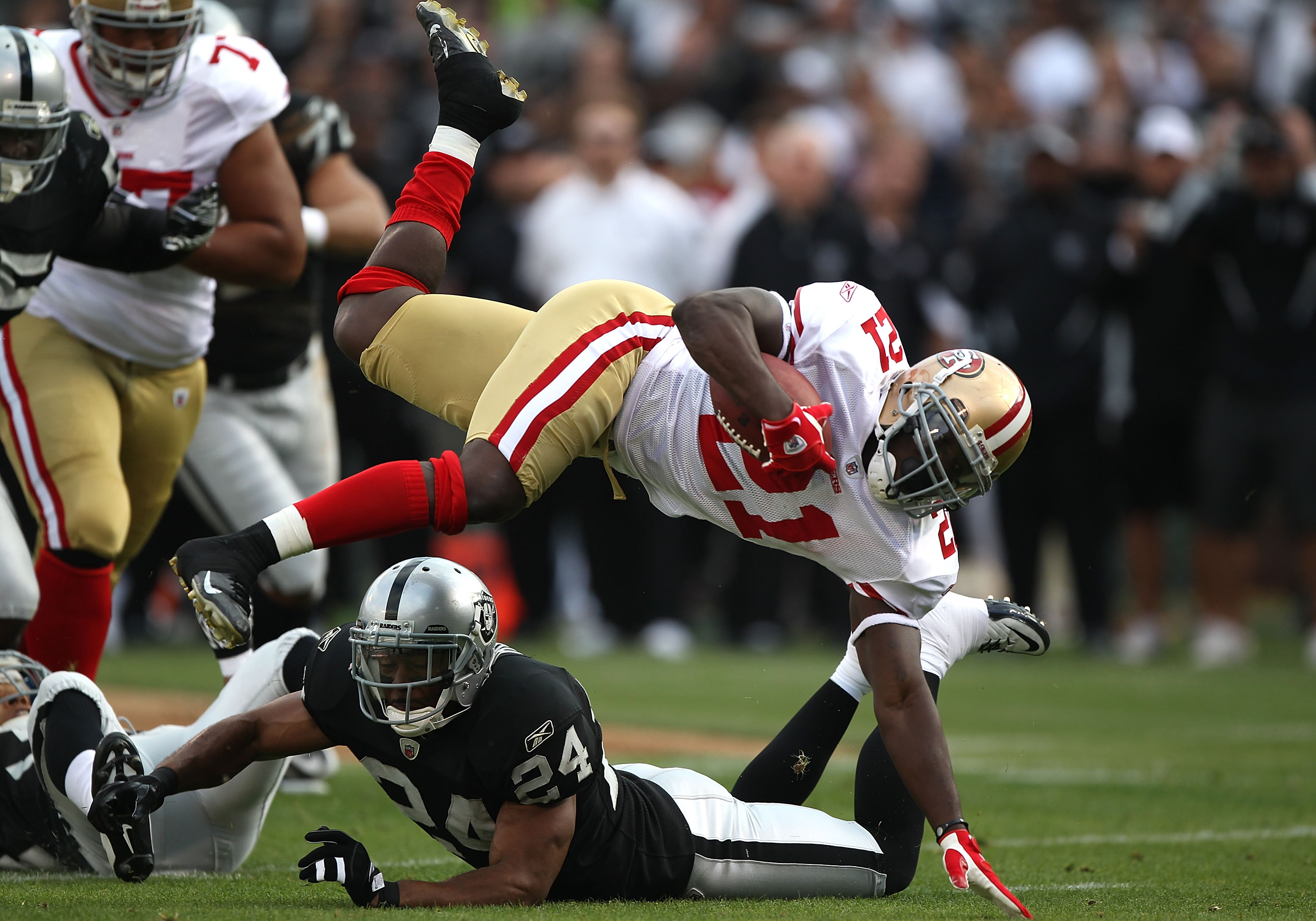 OAKLAND, CA - AUGUST 28:  Frank Gore #21 of the San Francisco 49ers runs against Michael Huff #24 of the Oakland Raiders during an NFL preseason game at Oakland-Alameda County Coliseum on August 28, 2010 in Oakland, California. (Photo by Jed Jacobsohn/Get
