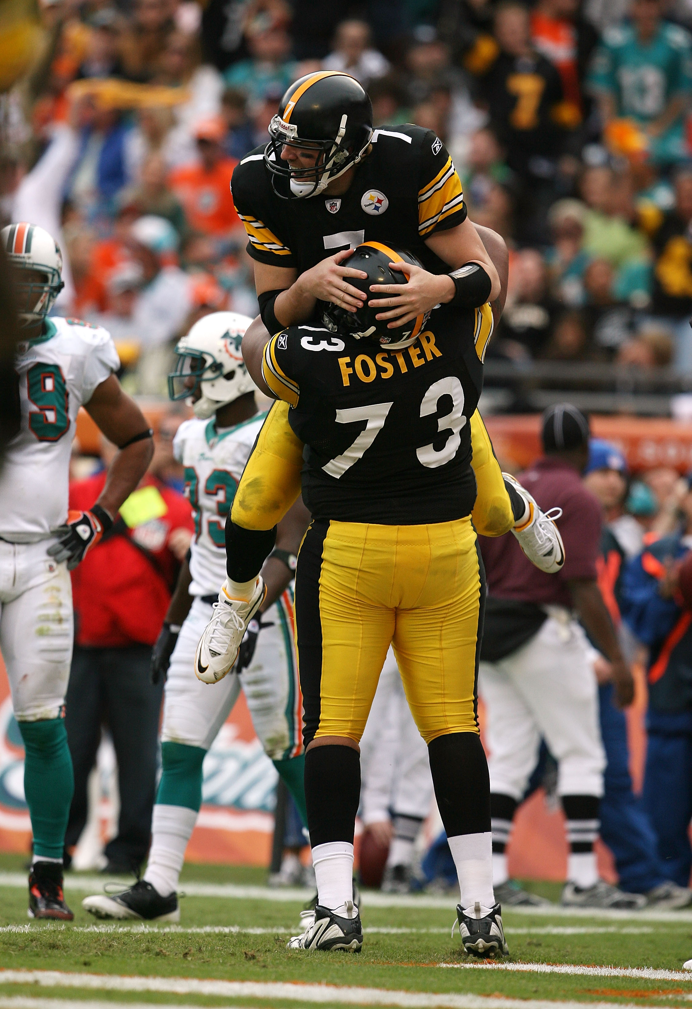 MIAMI - JANUARY 03:  Quarterback Ben Roethlisberger #7 of the Pittsburgh Steelers is lifted into the air by offensive linemen Ramon Foster #73 after Roethlisberger's touchdown pass to tight end Heath Miller #83 in the third quarter against the Miami Dolph