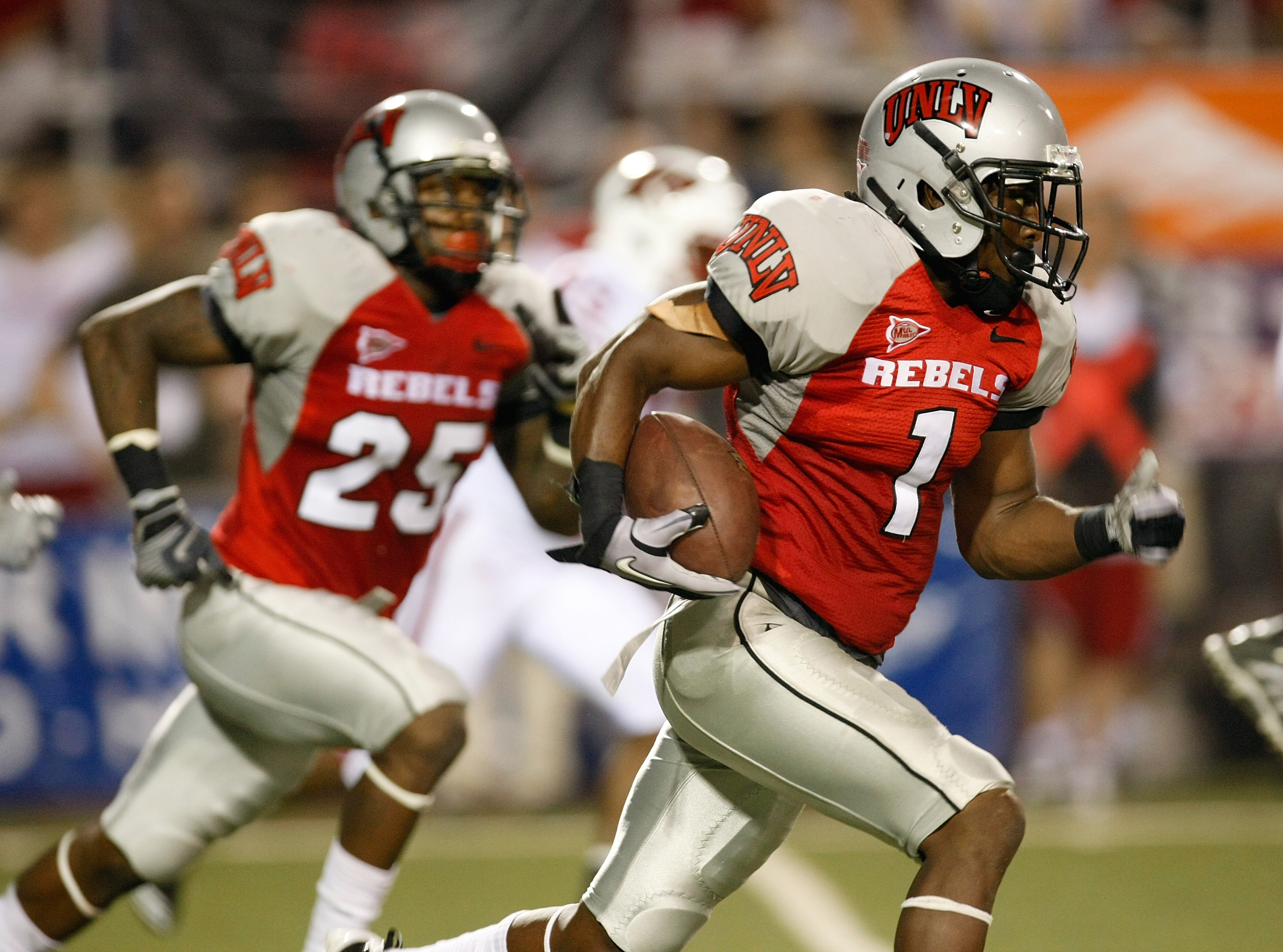 LAS VEGAS - SEPTEMBER 04:  Will Chandler #1 of the UNLV Rebels runs for yardage after recovering a fumble during the second quarter of their game against the Wisconsin Badgers at Sam Boyd Stadium September 4, 2010 in Las Vegas, Nevada. Mike Grant #25 of U