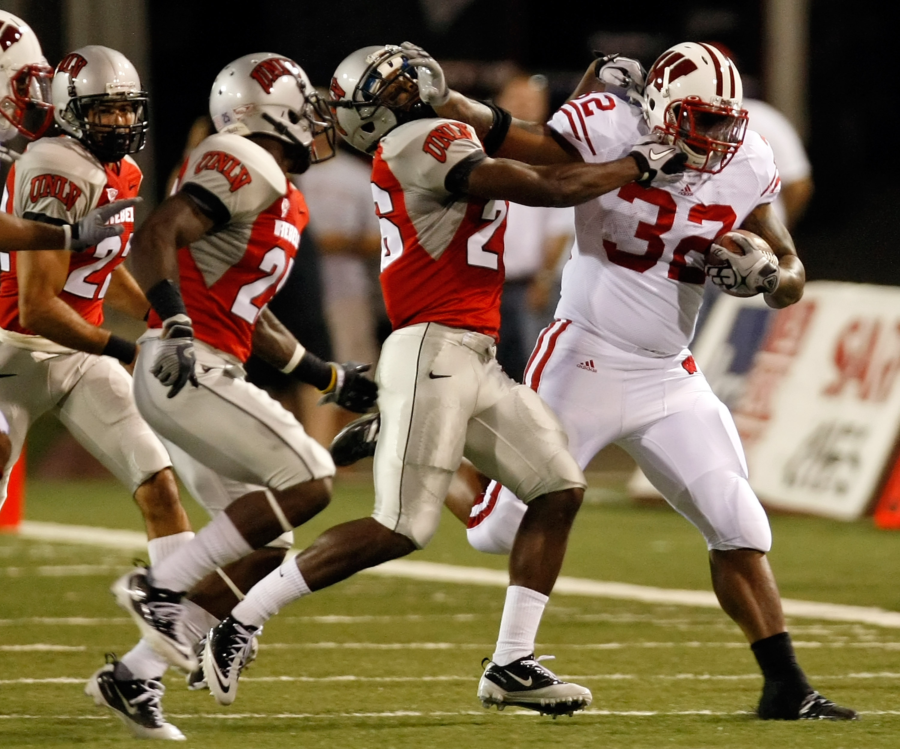 LAS VEGAS - SEPTEMBER 04:  John Clay #32 of the Wisconsin Badgers tries to get away from Deante' Purvis #26 of the UNLV Rebels during the first quarter of their game at Sam Boyd Stadium September 4, 2010 in Las Vegas, Nevada.  (Photo by Ethan Miller/Getty