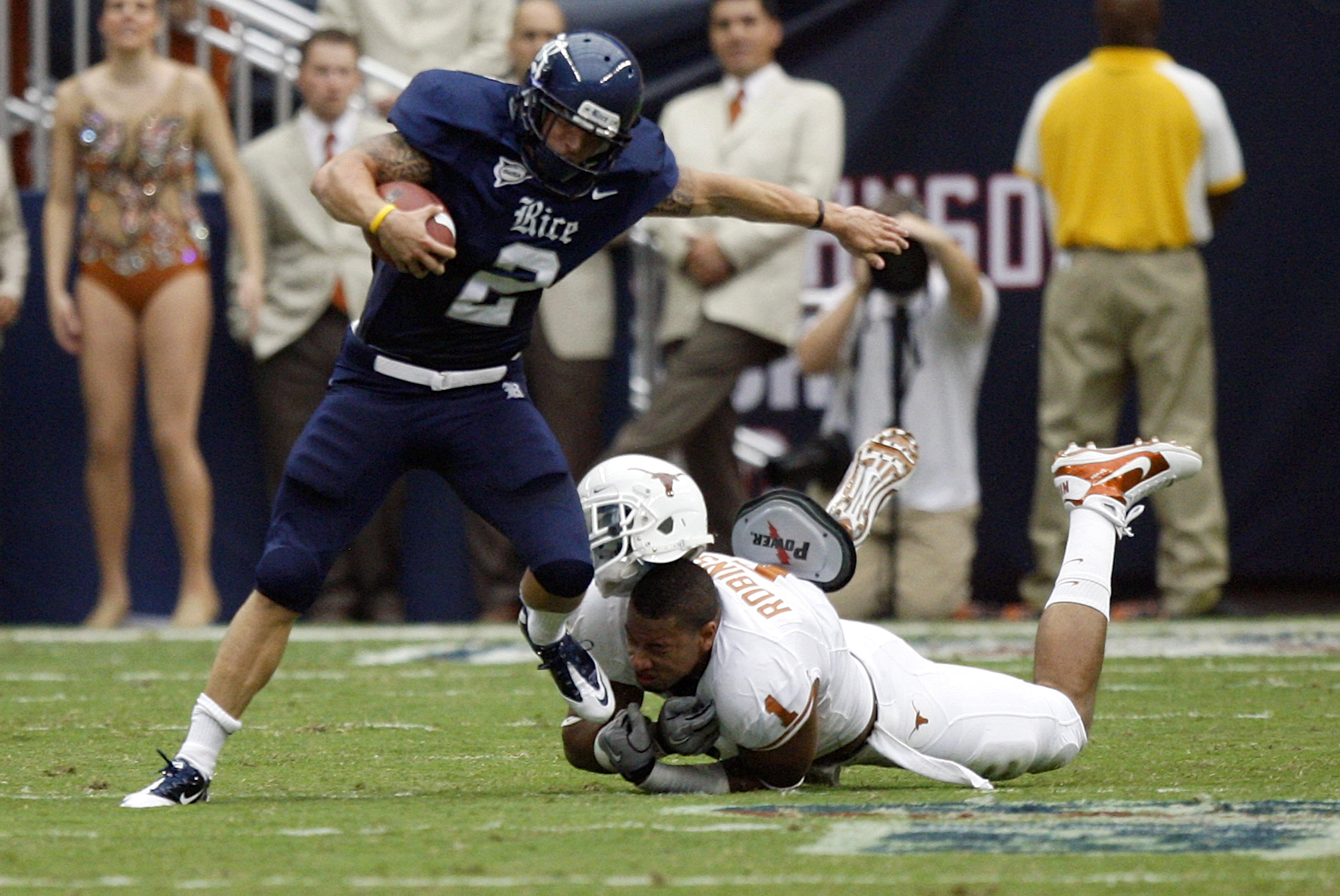 HOUSTON - SEPTEMBER 04:  Running back Sam McGuffie #2 of the Rice Owls is tackled by linebacker Keenan Robinson #1 of the Texas Longhorns at Reliant Stadium on September 4, 2010 in Houston, Texas.  (Photo by Bob Levey/Getty Images)