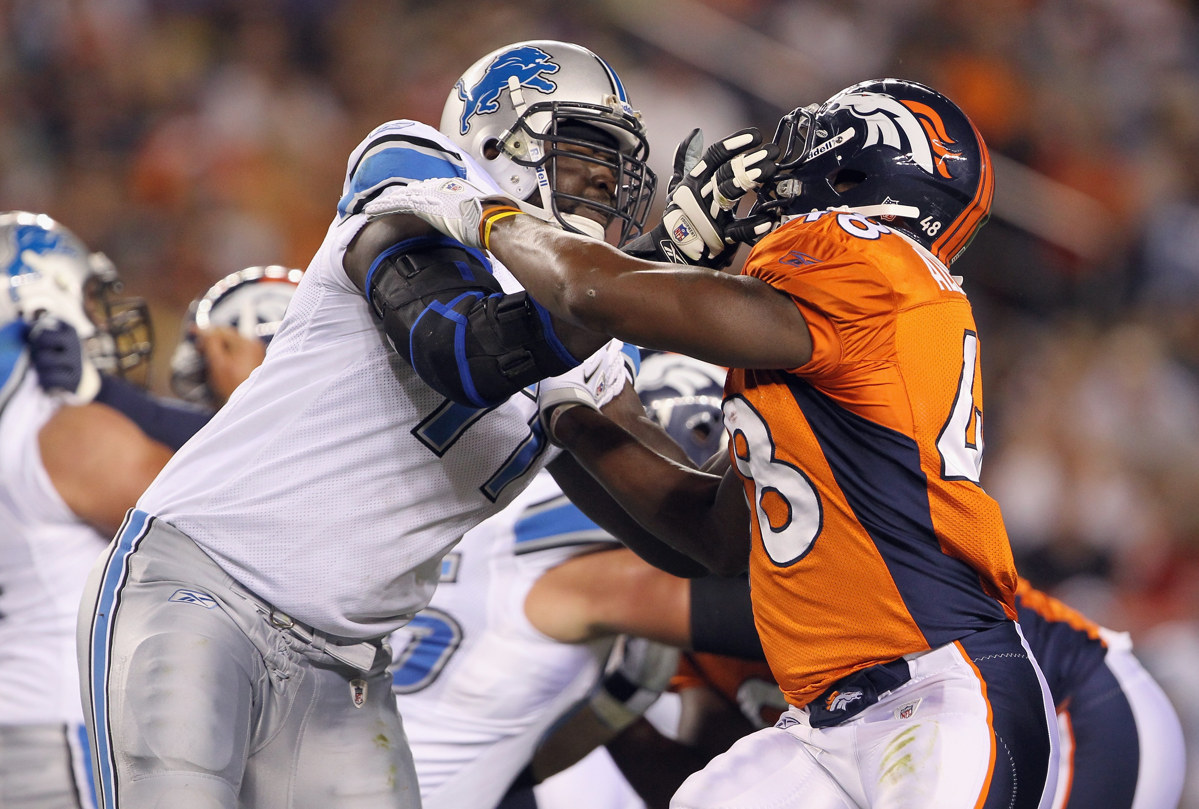 DENVER - AUGUST 21:  Offensive tackle Gosder Cherilus #77 of the Detroit Lions blocks the rush of Kevin Alexander #48 of the Denver Broncos during preseason NFL action at INVESCO Field at Mile High on August 21, 2010 in Denver, Colorado. The Lions defeate