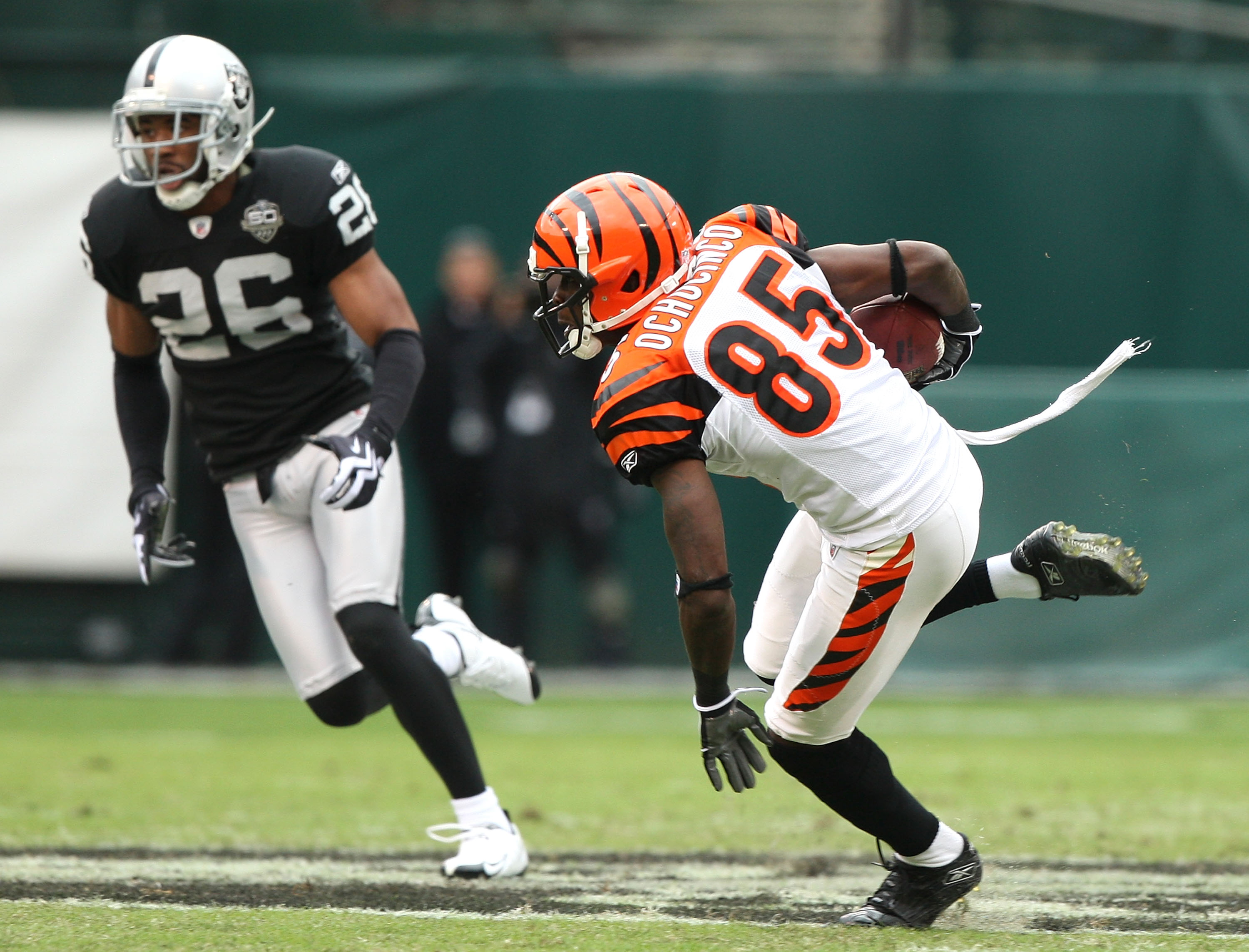 OAKLAND, CA - NOVEMBER 22:  Chad Ochocinco #85 of the Cincinnati Bengals runs after a catch against Stanford Routt #26 of the Oakland Raiders during an NFL game at Oakland-Alameda County Coliseum on November 22, 2009 in Oakland, California.  (Photo by Jed