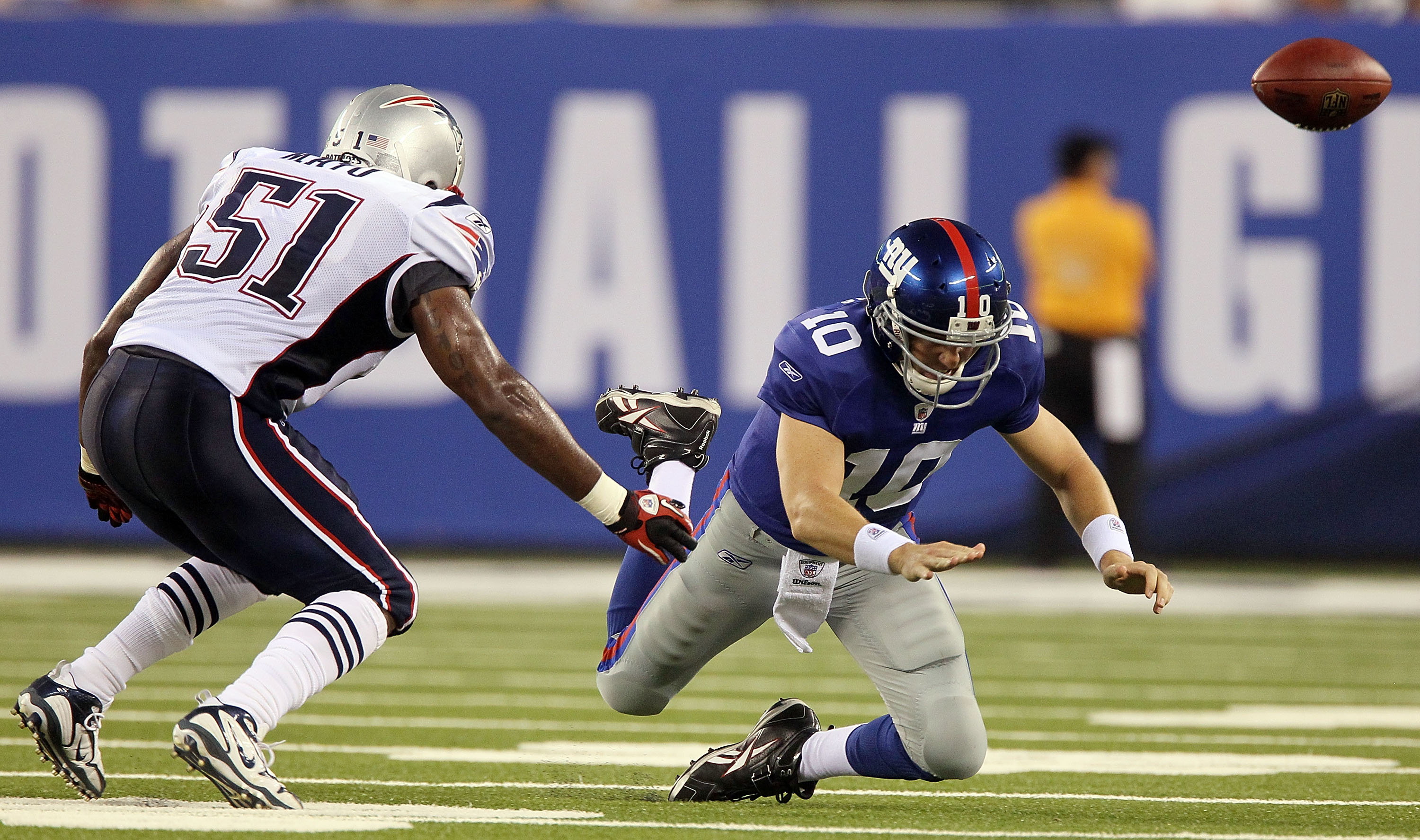 EAST RUTHERFORD, NJ - SEPTEMBER 02:  Eli Manning #10 of the New York Giants fumbles the ball in the first quarter as he is pressured by Jerod Mayo #51 of the New England Patriots on September 2, 2010 at the New Meadowlands Stadium in East Rutherford, New