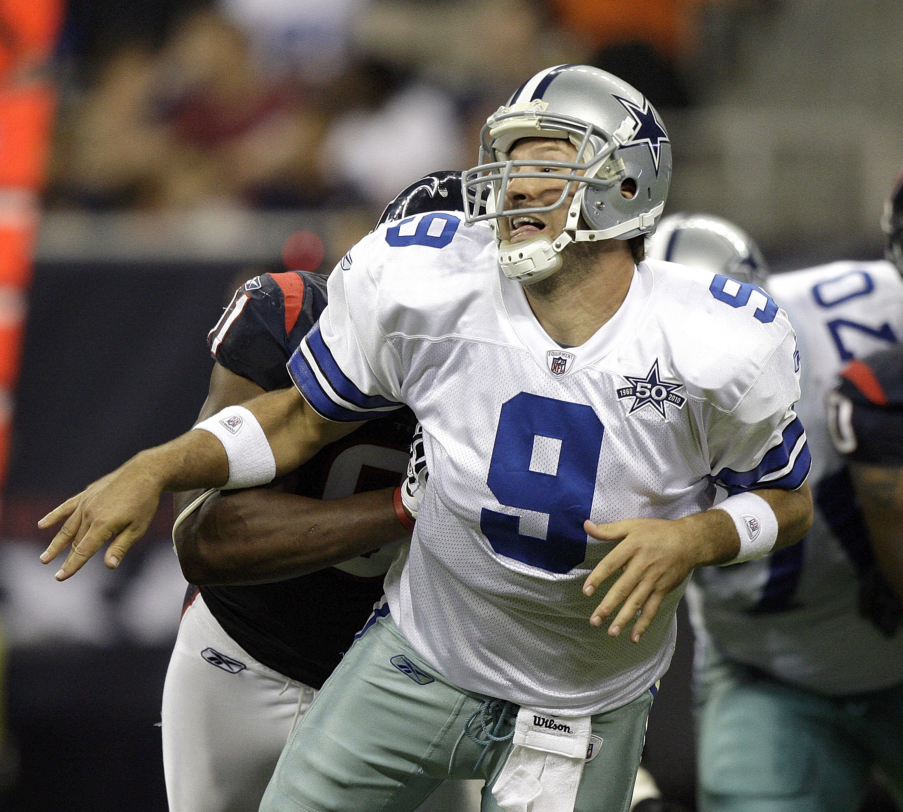 HOUSTON - AUGUST 28: Quarterback Tony Romo #9 of the Dallas Cowboys is hit from behind as he let's the ball go during a football game against the Houston Texans at Reliant Stadium on August 28, 2010 in Houston, Texas. Houston won 23-7. (Photo by Bob Levey