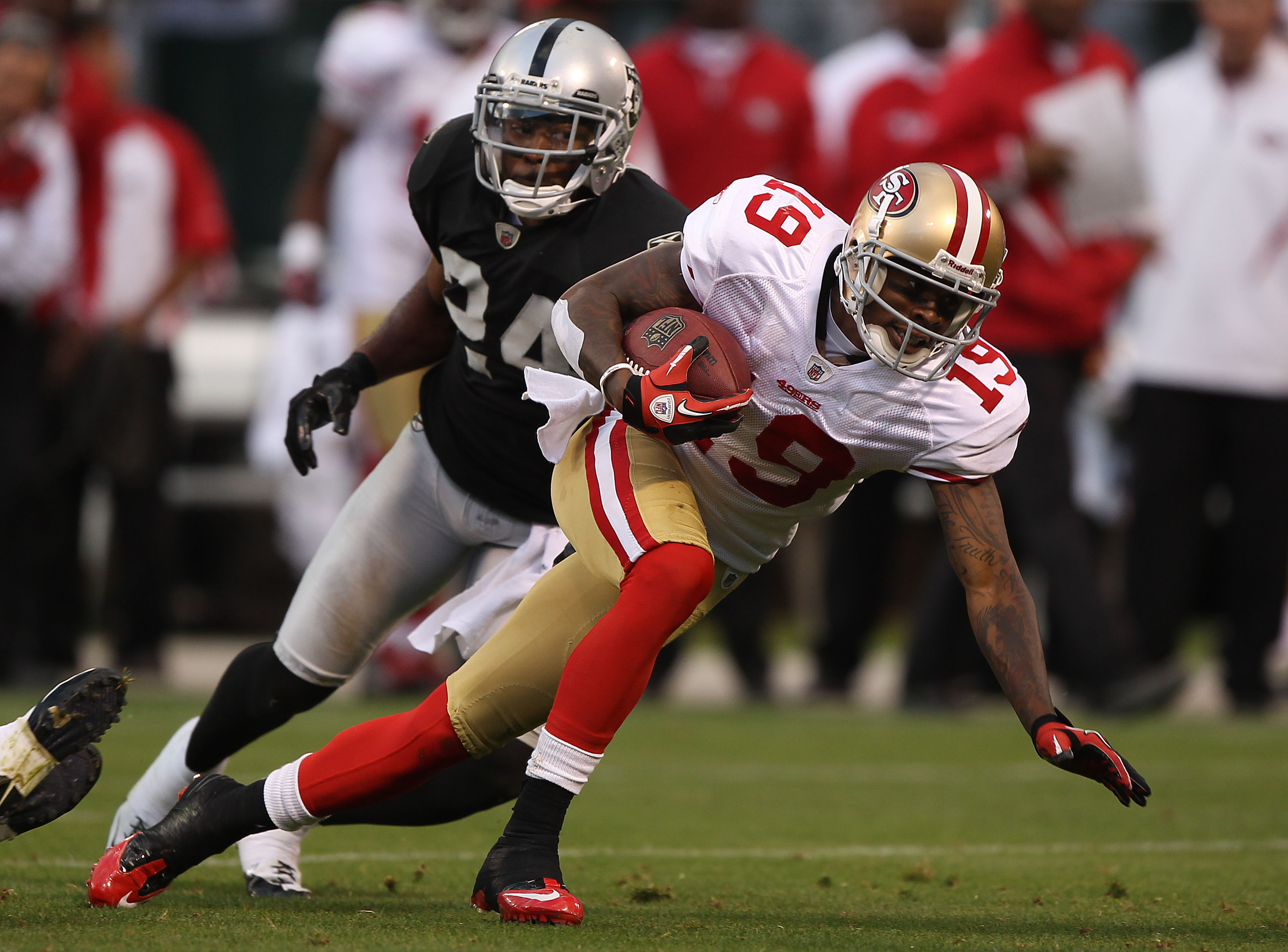 OAKLAND, CA - AUGUST 28: Ted Ginn #19 of the San Francisco 49er runs after a catch against Michael Huff #24 of the Oakland Raiders during an NFL preseason game at Oakland-Alameda County Coliseum on August 28, 2010 in Oakland, California. (Photo by Jed Jac