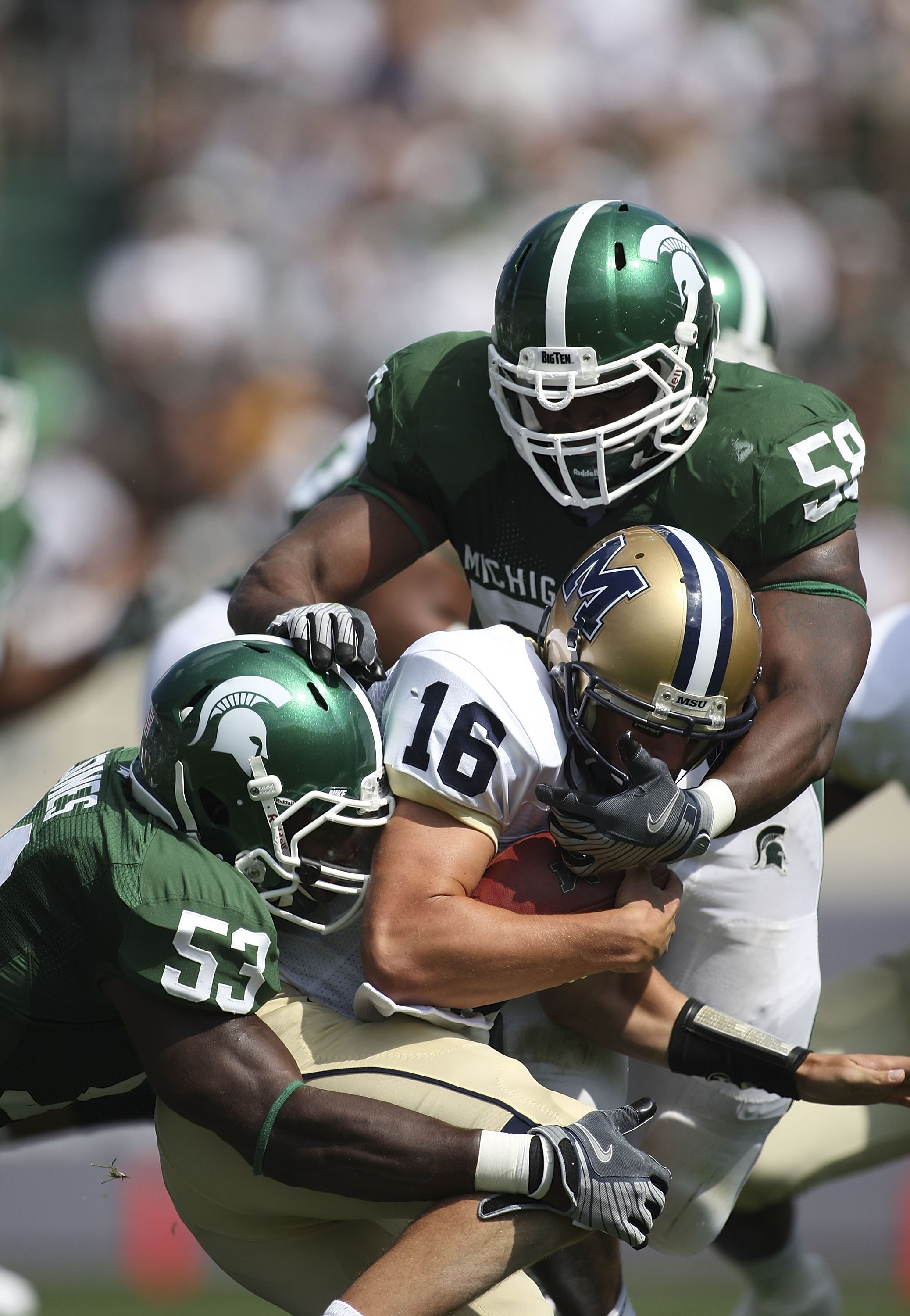 EAST LANSING, MI - SEPTEMBER 05: Tackle D.J. Young #59 and Linebacker Greg Jones #53 of the Michigan State Spartans sack Quarterback Mark Iddins #16 of Montana State during the second quarter on September 5, 2009 at Spartan Stadium in East Lansing, Michig