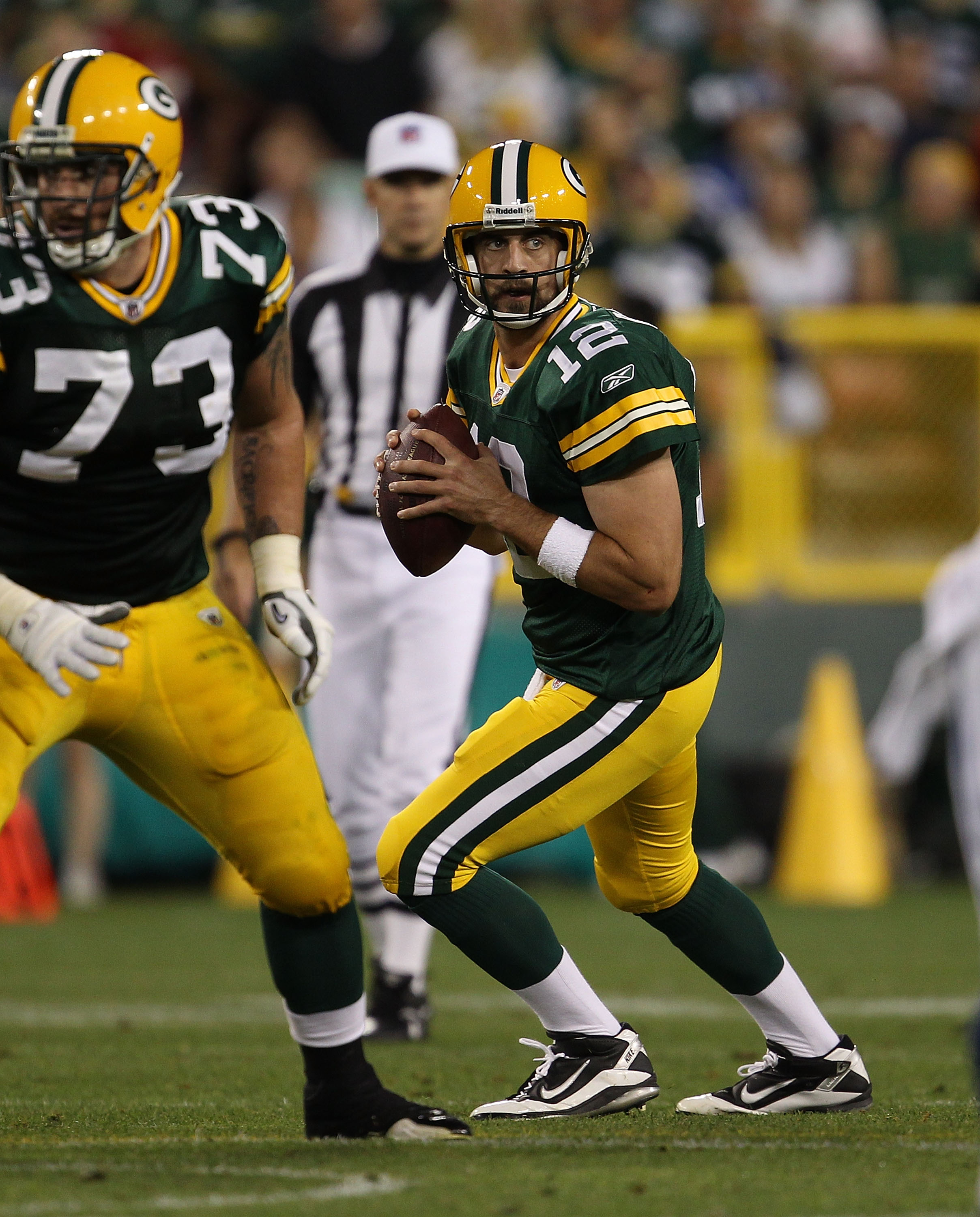 GREEN BAY, WI - AUGUST 26: Aaron Rodgers #12 of the Green Bay Packers drops back to look for a receiver as teammate Daryn Colledge #73 looks to block against the Indianapolis Colts during a preseason game at Lambeau Field on August 26, 2010 in Green Bay,