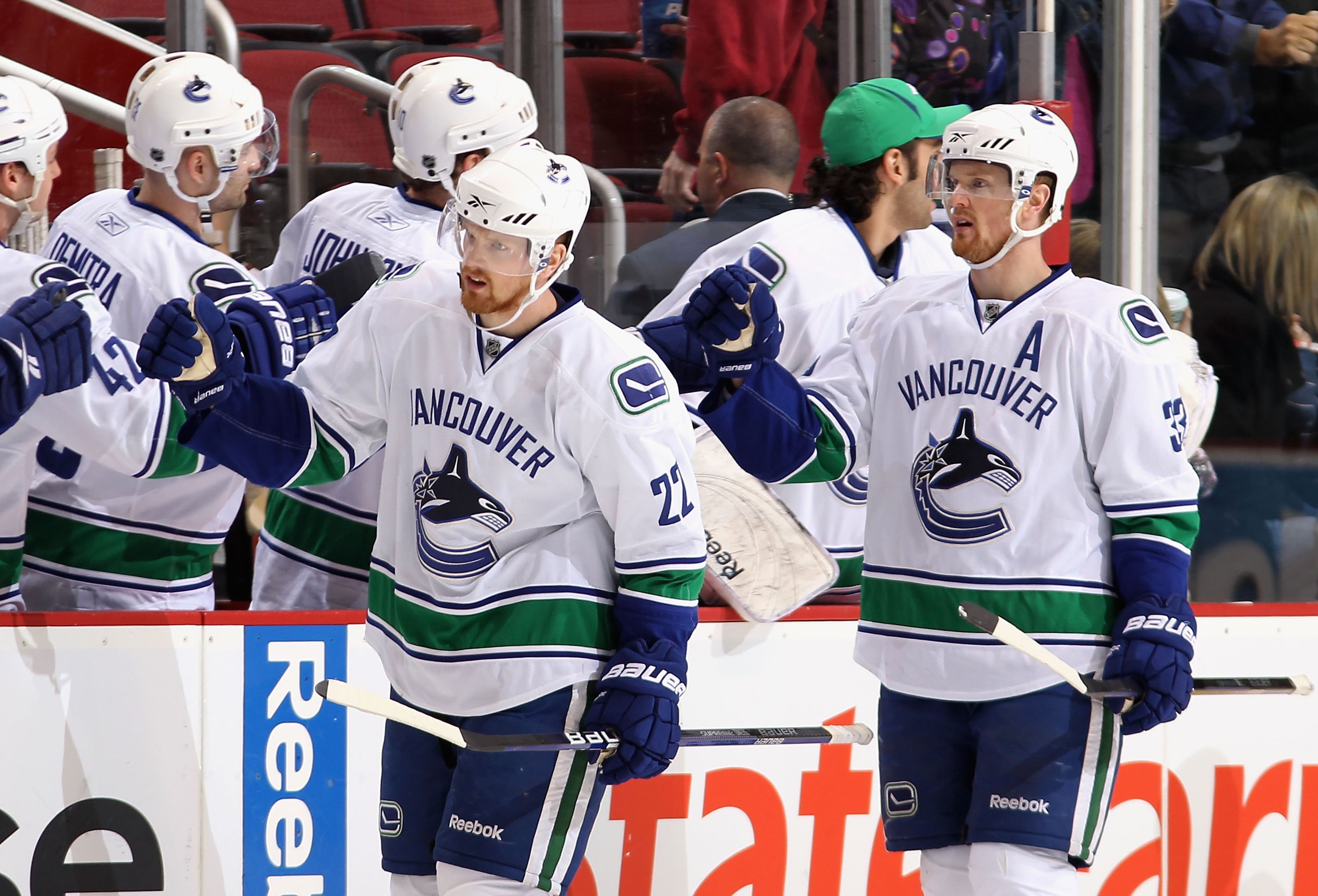 GLENDALE, AZ - MARCH 10:  Daniel Sedin #22 and Henrik Sedin #33 of the Vancouver Canucks celebrate with teammates after scoring during the NHL game against the Phoenix Coyotes at Jobing.com Arena on March 10, 2010 in Glendale, Arizona.  The Coyotes defeat