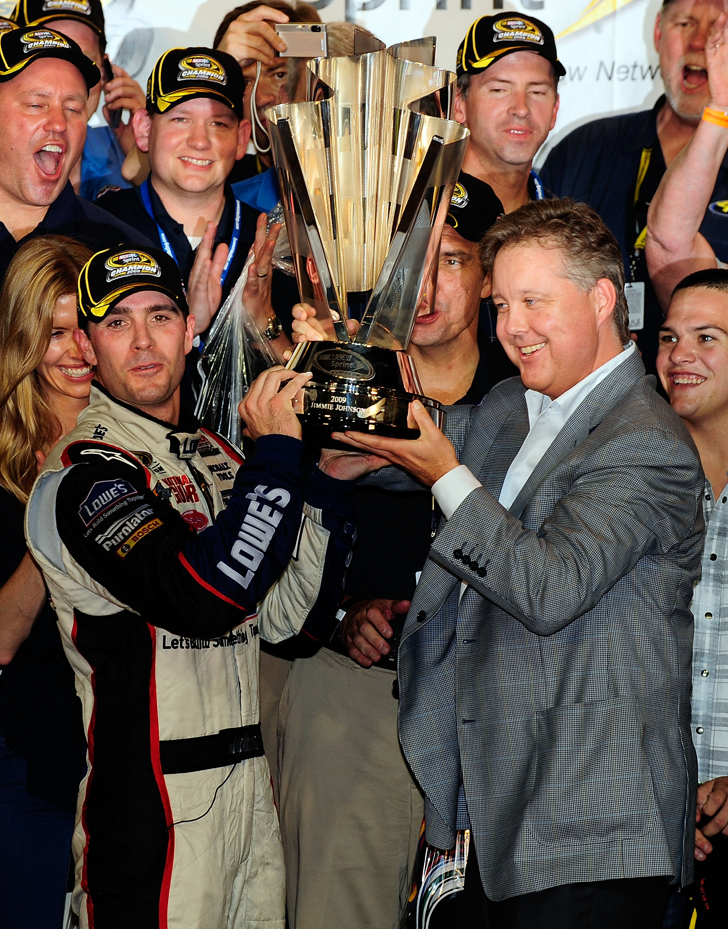 HOMESTEAD, FL - NOVEMBER 22:  Jimmie Johnson (L), driver of the #48 Lowe's Chevrolet, and NASCAR Chairman and CEO Brian France hoist the trophy after winning the NASCAR Sprint Cup Series Championship after finishing in fifth place in the Ford 400 at Homes