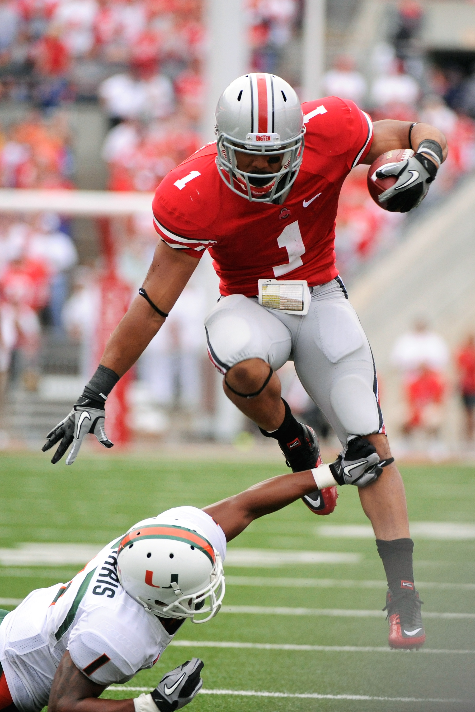 COLUMBUS, OH - SEPTEMBER 11:  Dan Herron #1 of the Ohio State Buckeyes leaps over the tackle attempt of Brandon Harris #1 of the Miami Hurricanes at Ohio Stadium on September 11, 2010 in Columbus, Ohio.  (Photo by Jamie Sabau/Getty Images)