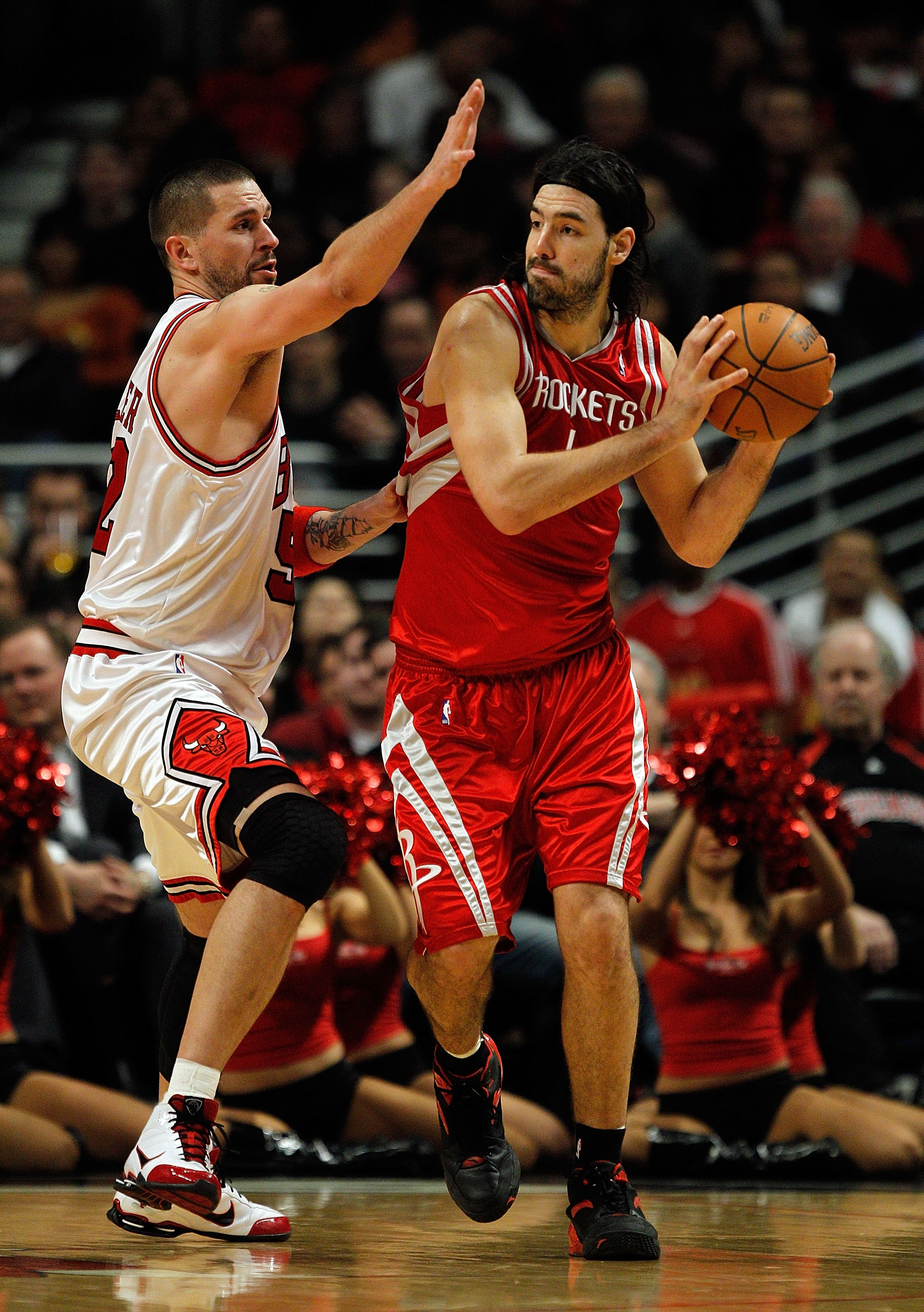 CHICAGO - MARCH 22: Luis Scola #4 of the Houston Rockets looks to pass under pressure from Brad Miller #52 of the Chicago Bulls at the United Center on March 22, 2010 in Chicago, Illinois. The Bulls defeated the Rockets 98-88. NOTE TO USER: User expressly