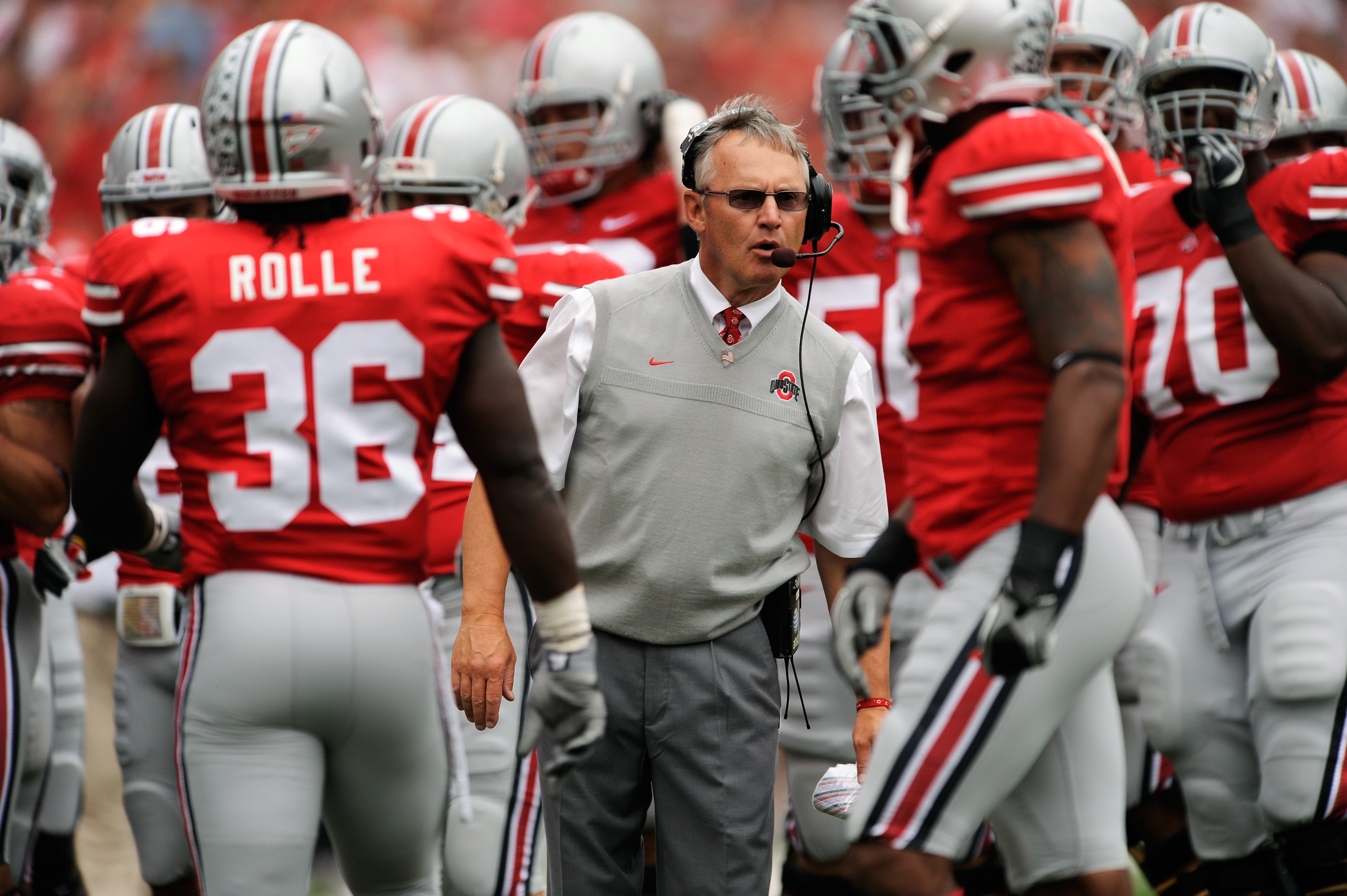 COLUMBUS, OH - SEPTEMBER 11:  Head Coach Jim Tressel (C) of the Ohio State Buckeyes gives instructions to his players as they play the Miami Hurricanes at Ohio Stadium on September 11, 2010 in Columbus, Ohio.  (Photo by Jamie Sabau/Getty Images)