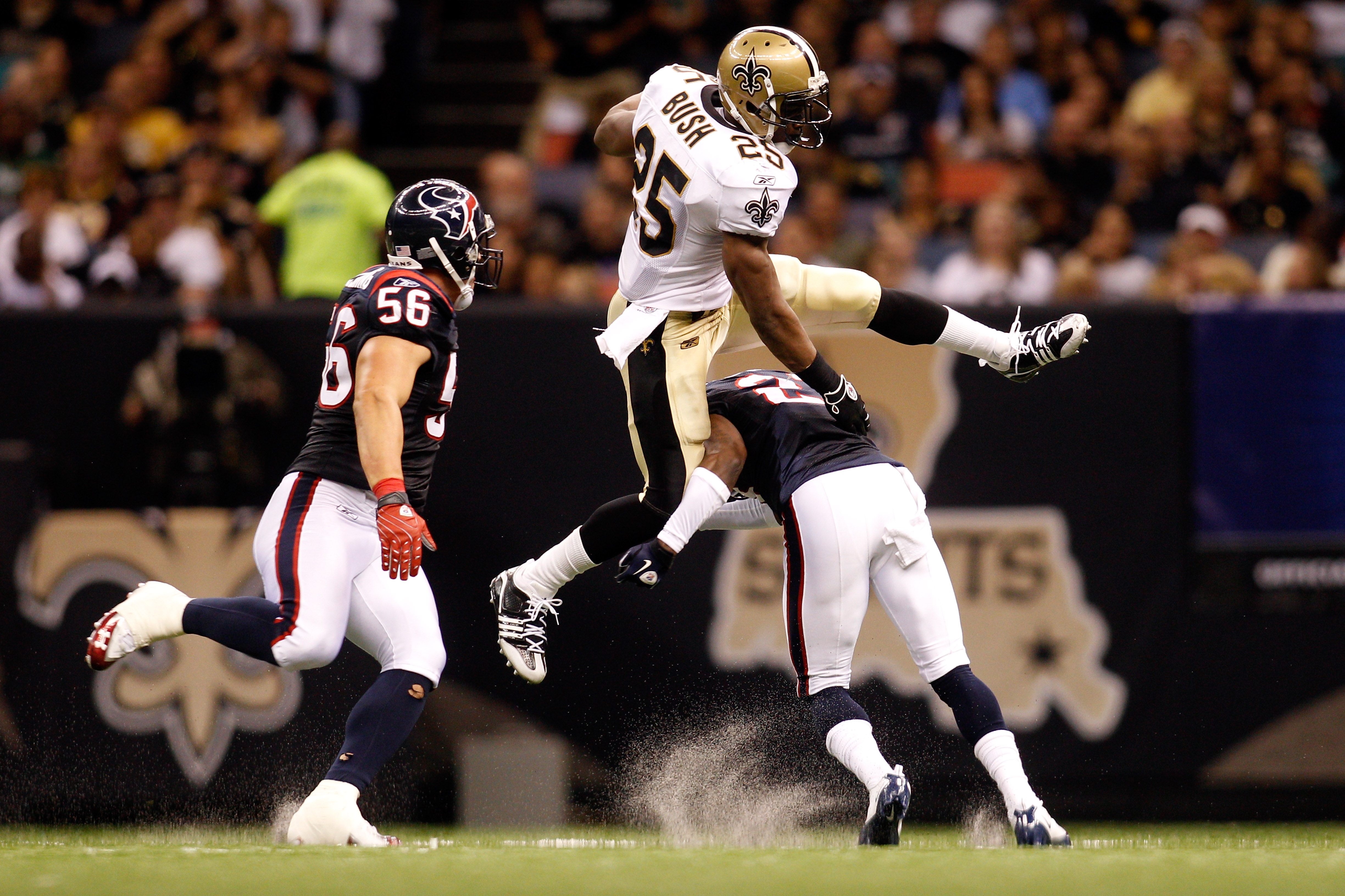 NEW ORLEANS - AUGUST 21:  Reggie Bush #25 of the New Orleans Saints jumps over Brice McCain #21 of the Houston Texans at the Louisiana Superdome on August 21, 2010 in New Orleans, Louisiana.  (Photo by Chris Graythen/Getty Images)