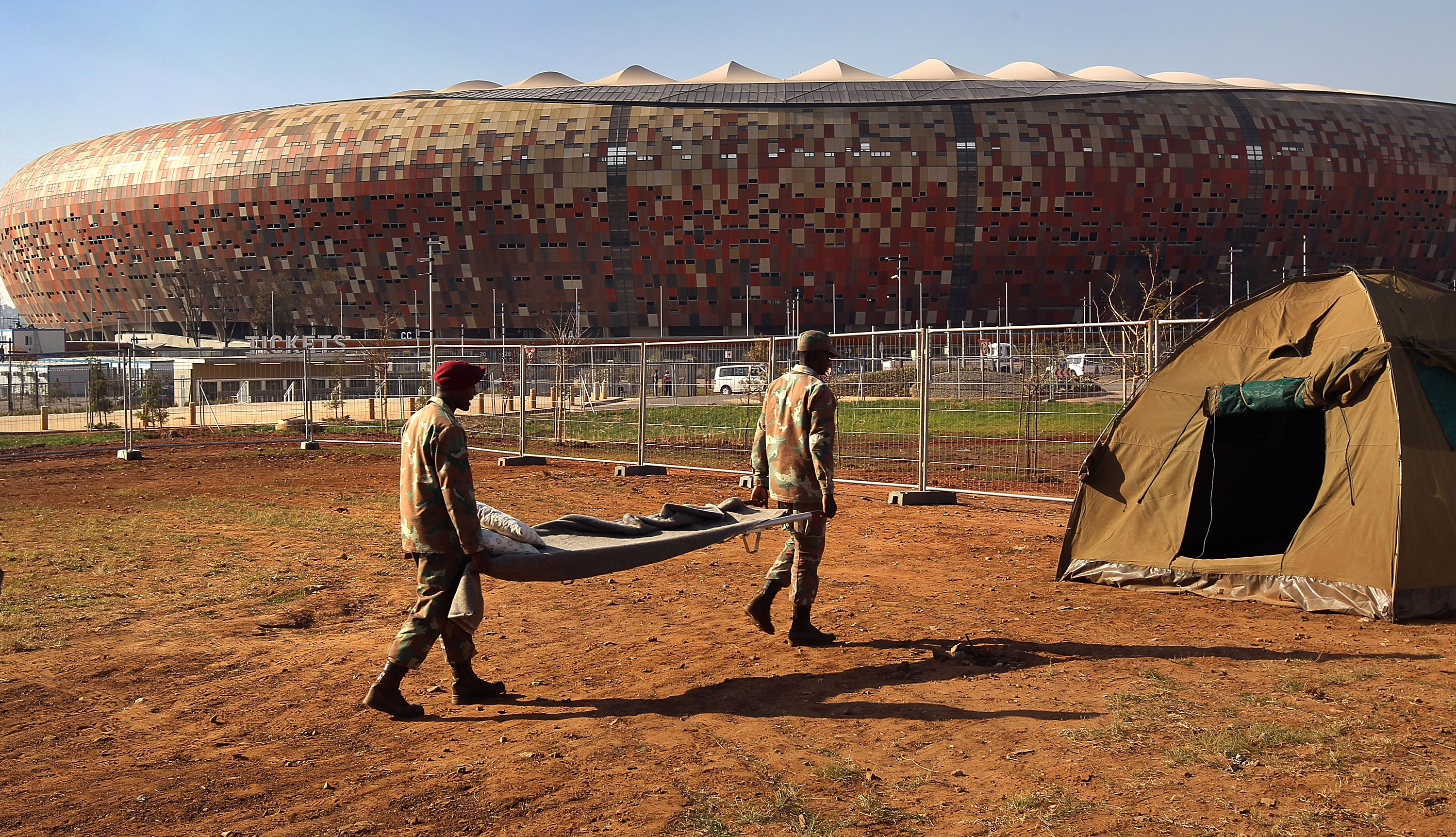 JOHANNESBURG, SOUTH AFRICA - JUNE 03:  South African army troops carry a stretcher while setting up a medical center outside the Soccer City stadium on June 3, 2010 in Johannesburg, South Africa. The medical center, to be staffed by the military, is prepa