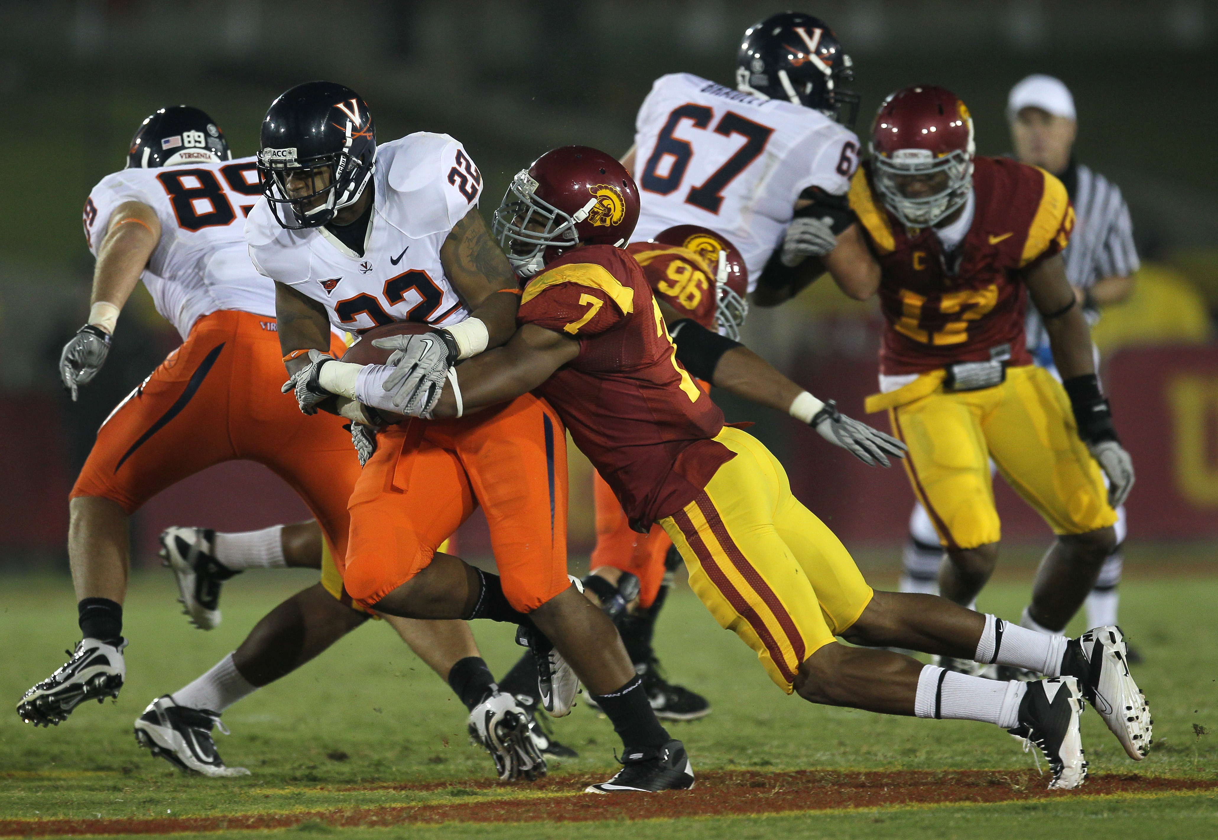 LOS ANGELES, CA - SEPTEMBER 11:  Safety T.J. McDonald #7 of the USC Trojans tackles running back Keith Payne #22 of the Virginia Cavaliers at Los Angeles Memorial Coliseum on September 11, 2010 in Los Angeles, California.  (Photo by Stephen Dunn/Getty Ima