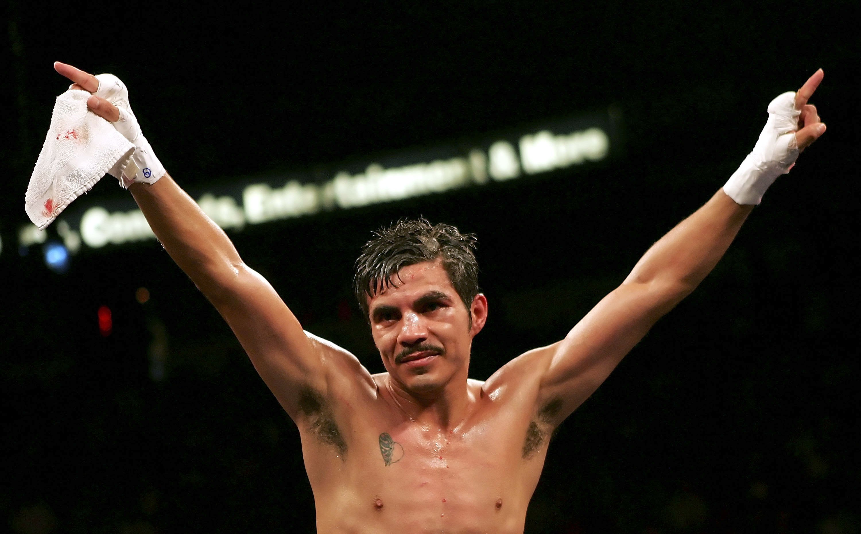 LAS VEGAS - NOVEMBER 18:  (R-L) Omar Nino of Mexico puts his arms up in celebration after his light flyweight title bout against Brian Viloria at the Thomas & Mack Center on November 18, 2006 in Las Vegas, Nevada. Nino won by majority draw to remain WBC c