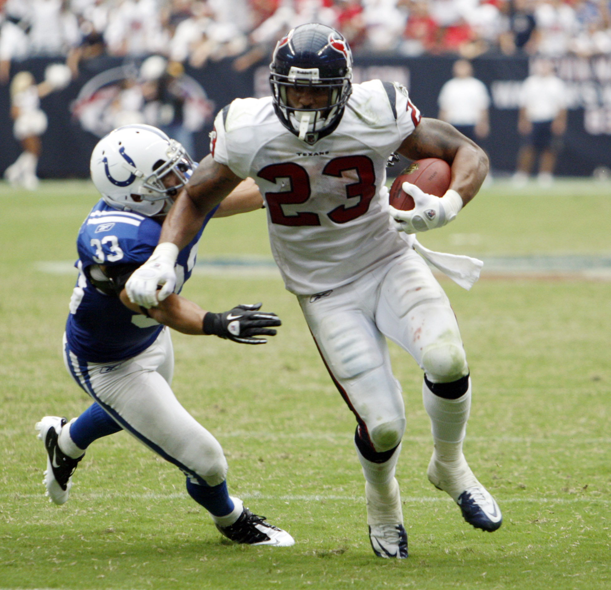 HOUSTON - SEPTEMBER 12:  Running back Arian Foster #23 of the Houston Texans avoids a tackle by defensive back Melivn Bullitt #33 of the Indianapolis Colts during the NFL season opener at Reliant Stadium on September 12, 2010 in Houston, Texas.  (Photo by