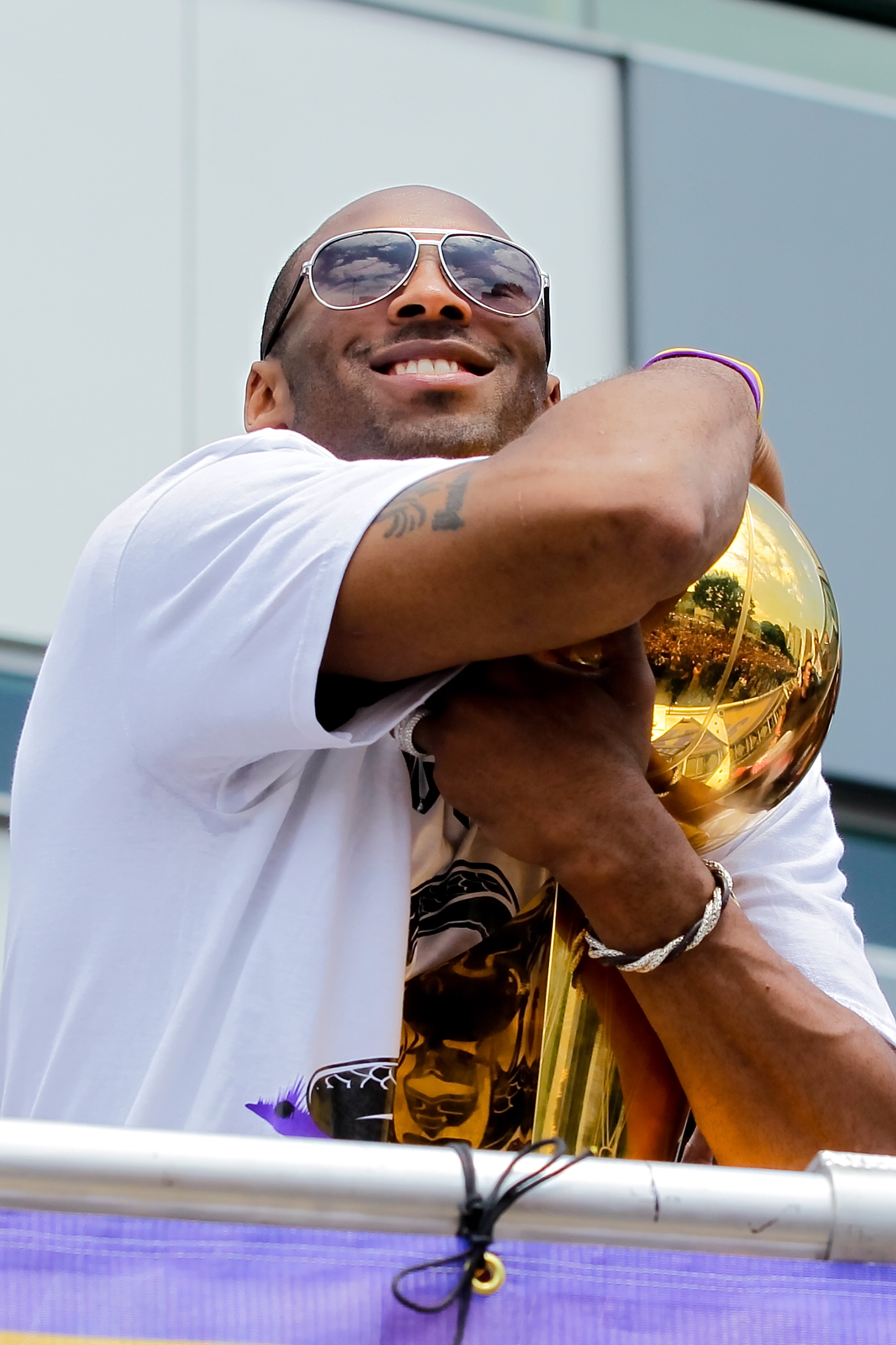 LOS ANGELES, CA - JUNE 21:  Los Angeles Lakers guard Kobe Bryant holds the championship trophy while riding in the victory parade for the the NBA basketball champion team on June 21, 2010 in Los Angeles, California. The Lakers beat the Boston Celtics 87-7