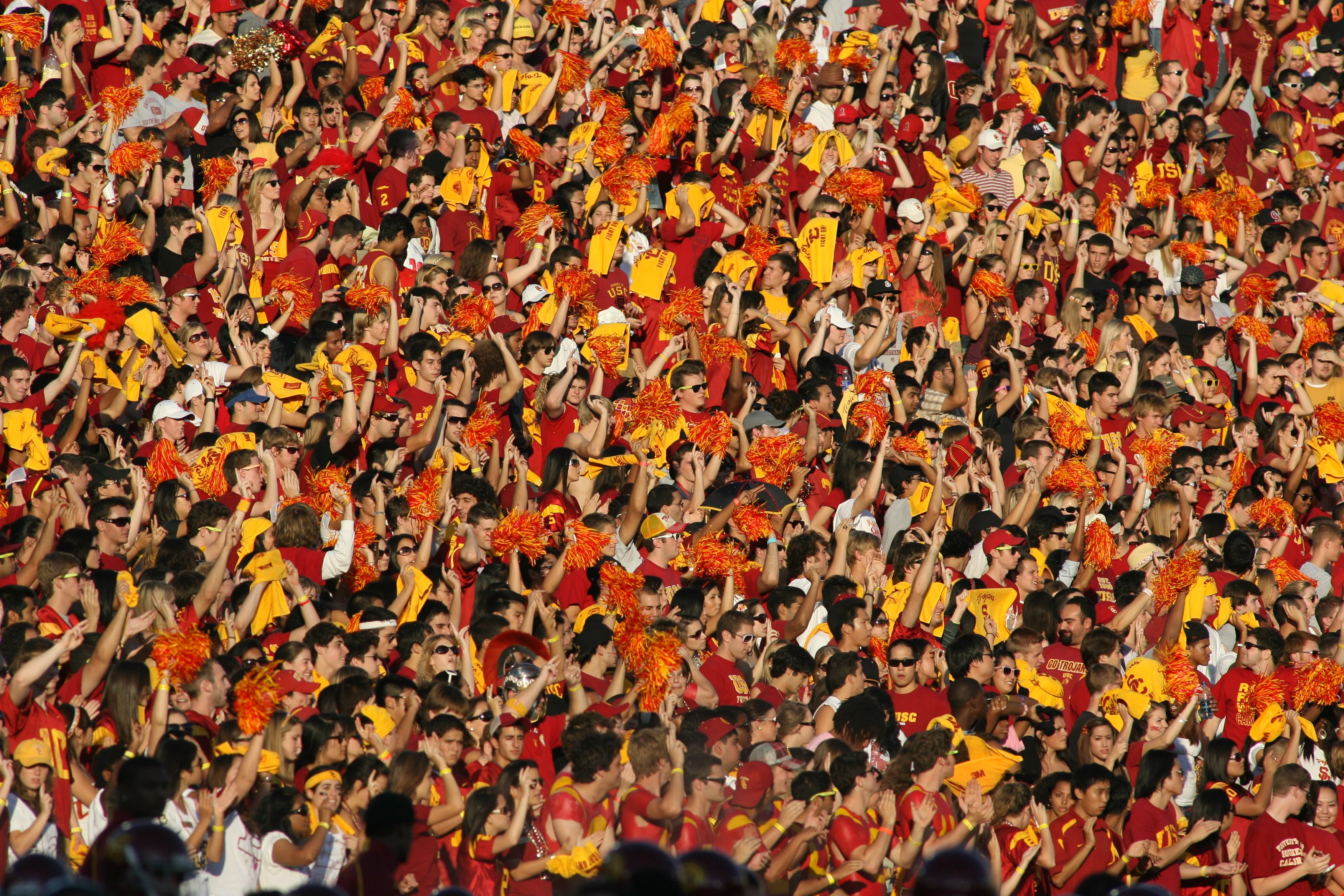LOS ANGELES, CA - OCTOBER 24:  Fans of the USC Trojans dressed in team colors wave pon pons and yellow towels in the autumn sun during the game against the Oregon State Beavers on October 24, 2009 at the Los Angeles Coliseum in Los Angeles, California.  U