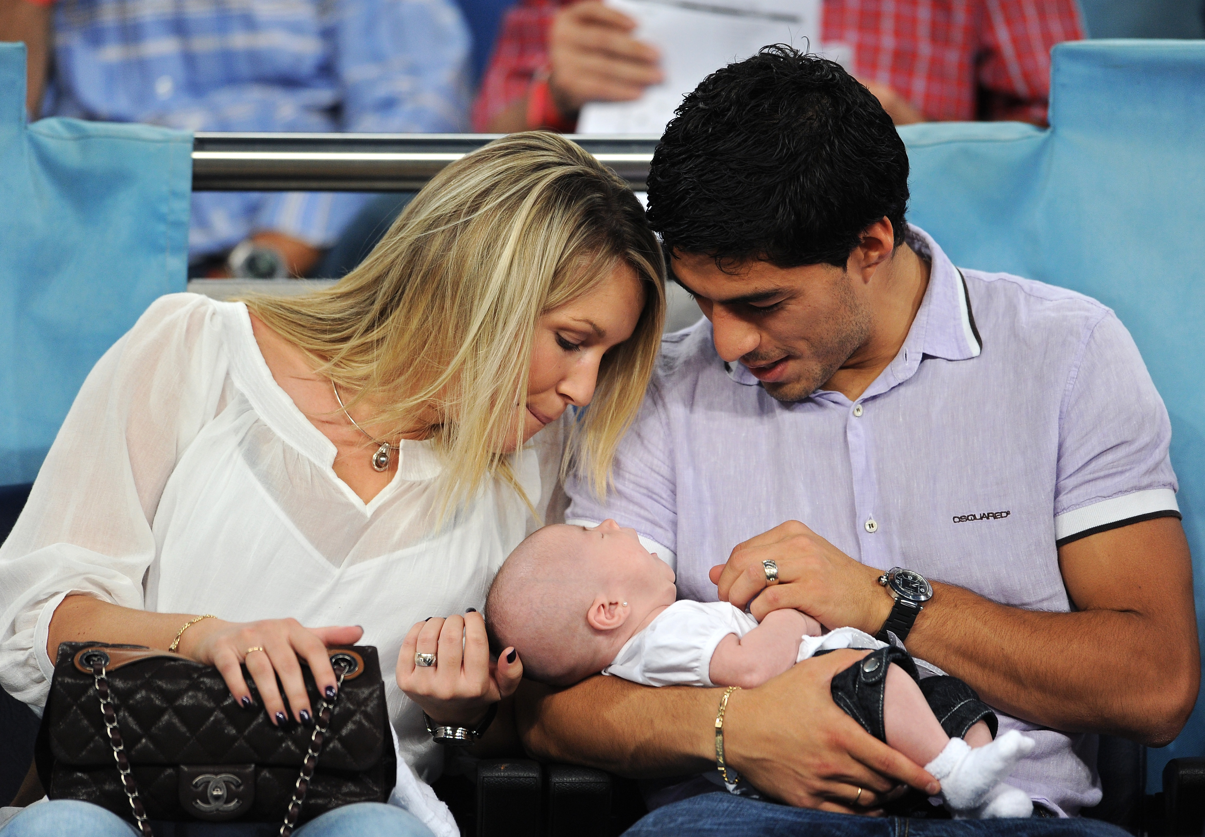 MADRID, SPAIN - SEPTEMBER 15: Expelled Ajax player Luis Suarez (R) hold his baby daughter Delfina while seated next to his wife Sofia prior to the start of the UEFA Champions League group G match between Real Madrid and Ajax at the Estadio Santiago Bernab