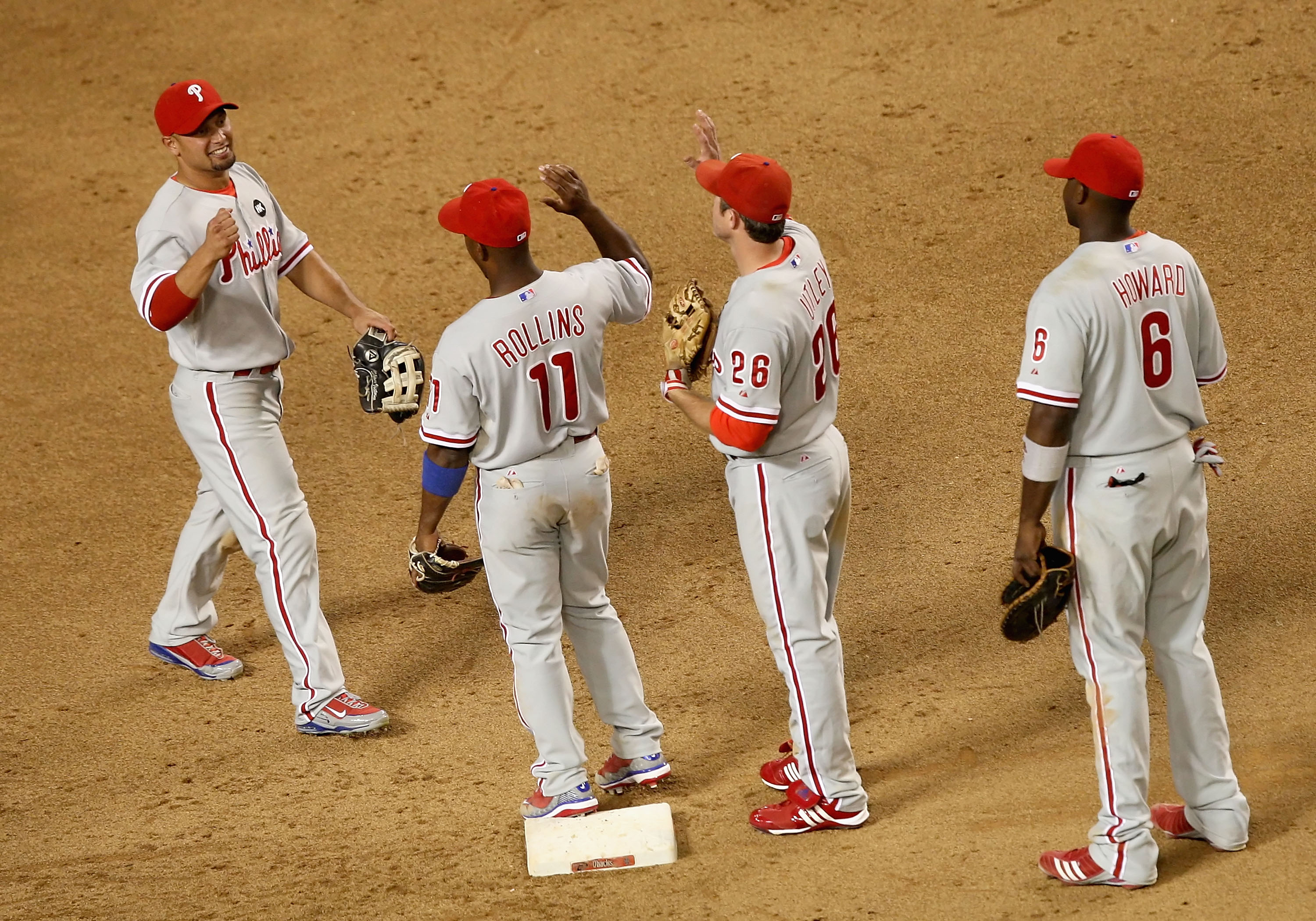 PHOENIX - JULY 28:  (L-R) Shane Victorino #8 of the Philadelphia Phillies celebrates with teammates Jimmy Rollins #11, Chase Utley #26 and Ryan Howard #6 after defeating the Arizona Diamondbacks during the major league baseball game at Chase Field on July