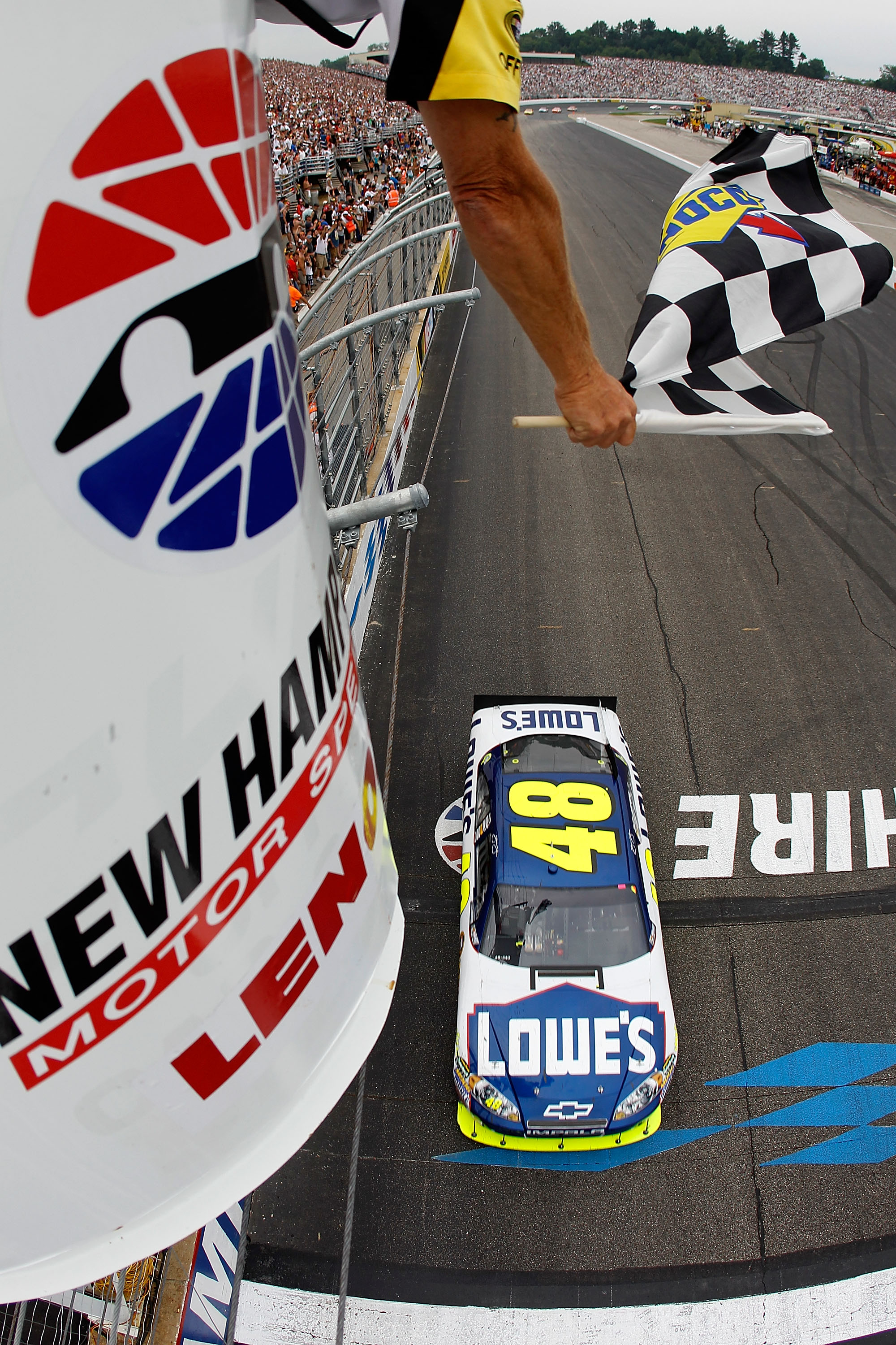 LOUDON, NH - JUNE 27:  Jimmie Johnson, driver of the #48 Lowe's Chevrolet, takes the checkered flag to win the NASCAR Sprint Cup Series LENOX Industrial Tools 301 at New Hampshire Motor Speedway on June 27, 2010 in Loudon, New Hampshire.  (Photo by Todd W