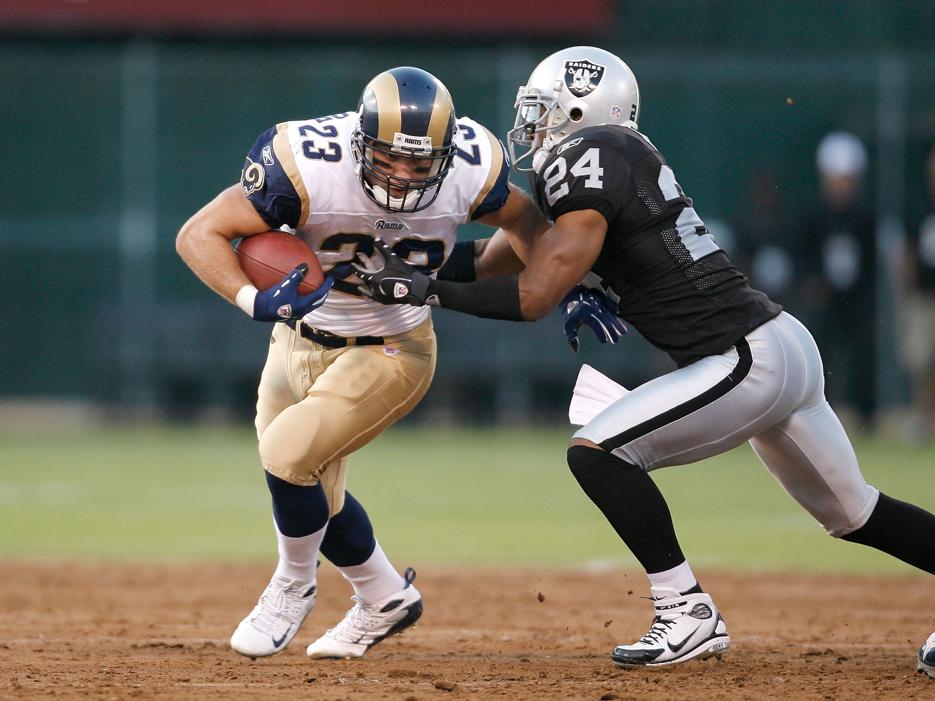 OAKLAND, CA - AUGUST 24:  Running back Brian Leonard #23 of the St. Louis Rams fights for yards as defensive back Michael Huff #24 of the Oakland Raiders tackles him during a preseason game on August 24, 2007 at McAfee Coliseum in Oakland, California.  (P