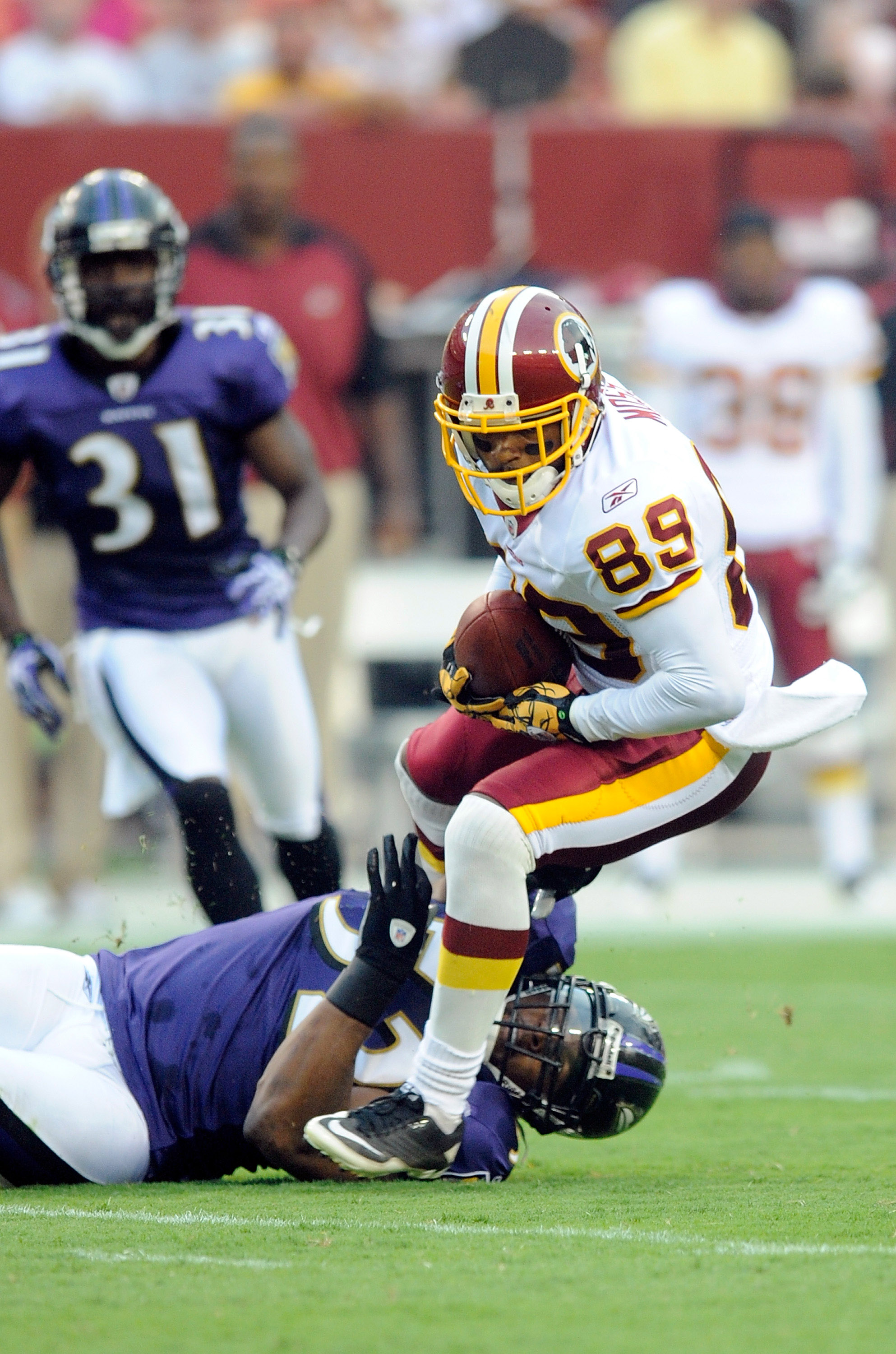LANDOVER, MD - AUGUST 21:  Santana Moss #89 of the Washington Redskins is tackled during the preseason game by Ray Lewis #52 of the Baltimore Ravens at FedExField on August 21, 2010 in Landover, Maryland.  (Photo by Greg Fiume/Getty Images)