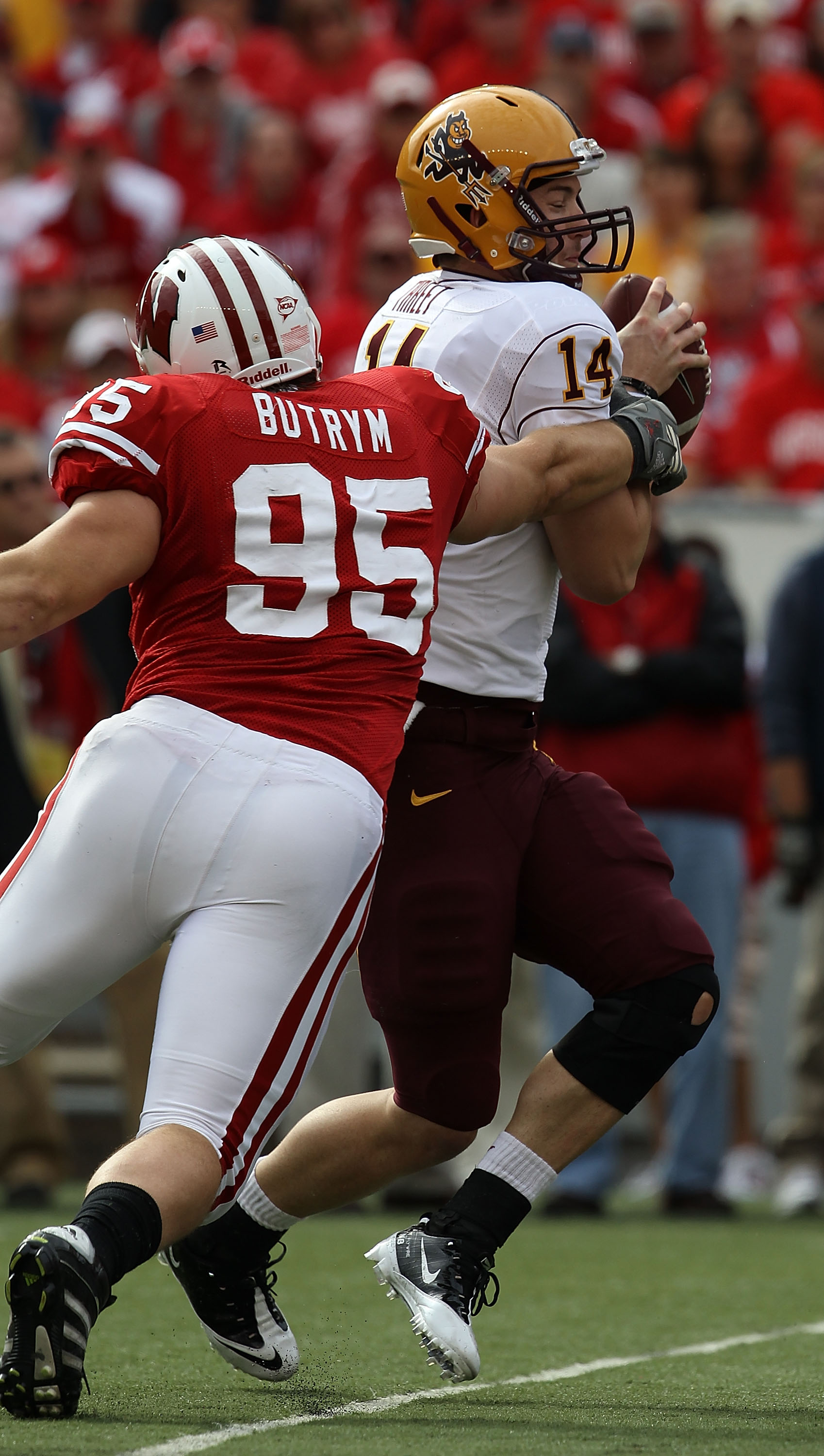 MADISON, WI - SEPTEMBER 18: Patirck Butrym #95 of the Wisconsin Badgers grabs Steven Threet #14 of the Arizona State Sun Devils as he looks for a receiver at Camp Randall Stadium on September 18, 2010 in Madison, Wisconsin. Wisconsin defeated Arizona Stat