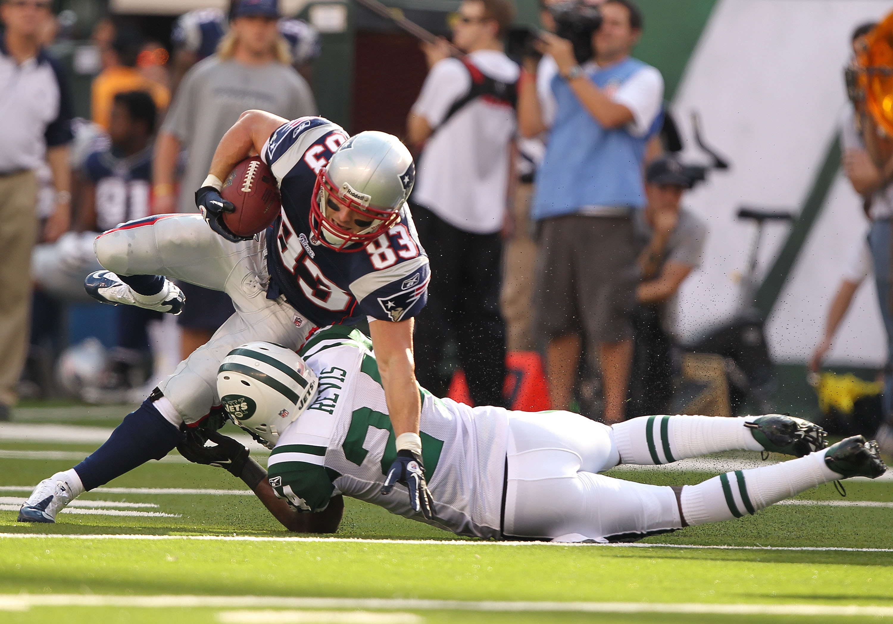 EAST RUTHERFORD, NJ - SEPTEMBER 19:  Darrelle Revis #24 of the New York Jets tackles Wes Welker #83 of the New England Patriots during their  game on September 19, 2010 at the New Meadowlands Stadium  in East Rutherford, New Jersey.  (Photo by Al Bello/Ge