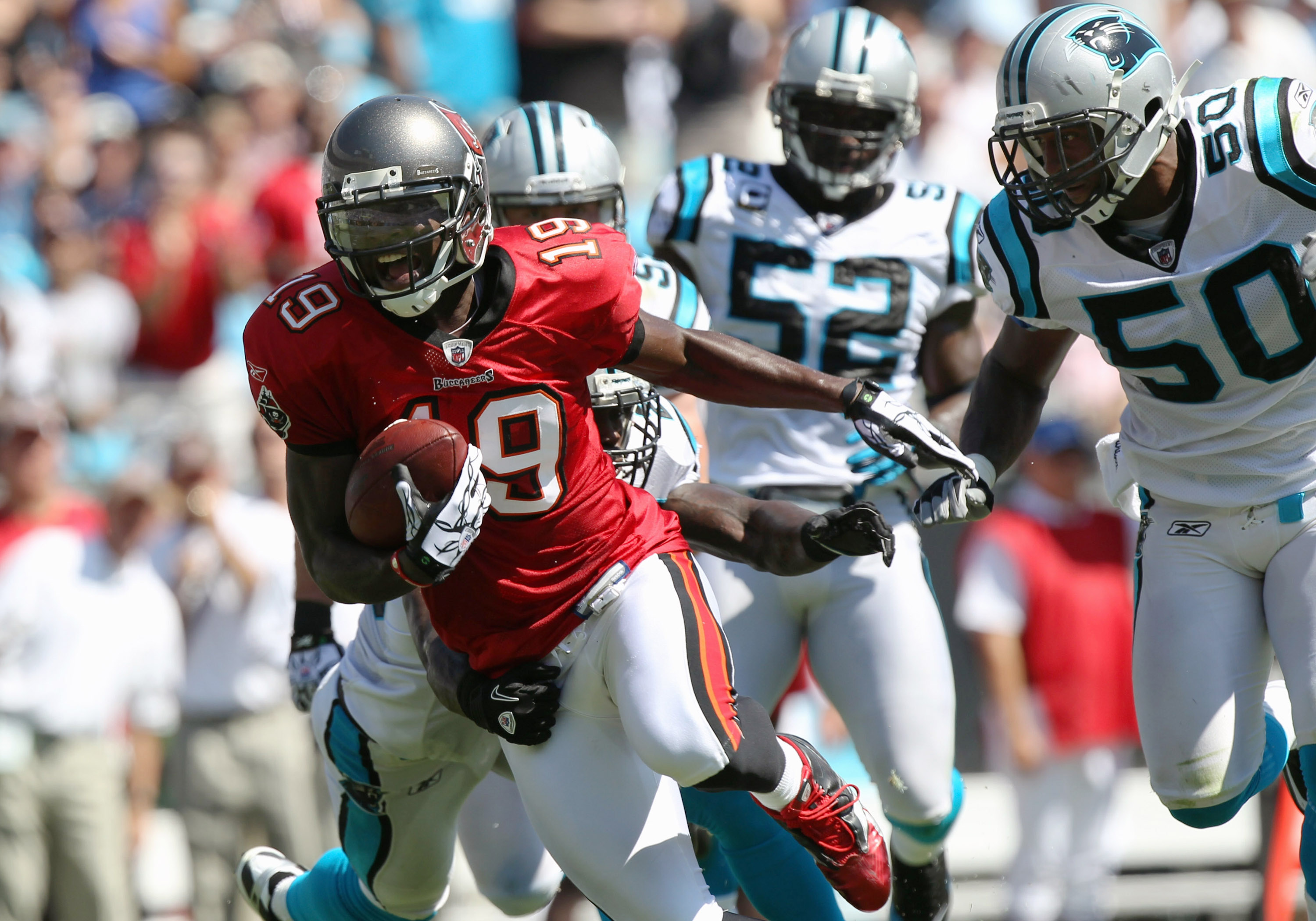 CHARLOTTE, NC - SEPTEMBER 19:  Mike Williams #19 of the Tampa Bay Buccaneers breaks a tackle on his way to scoring a touchdown against the Carolina Panthers during their game at Bank of America Stadium on September 19, 2010 in Charlotte, North Carolina.