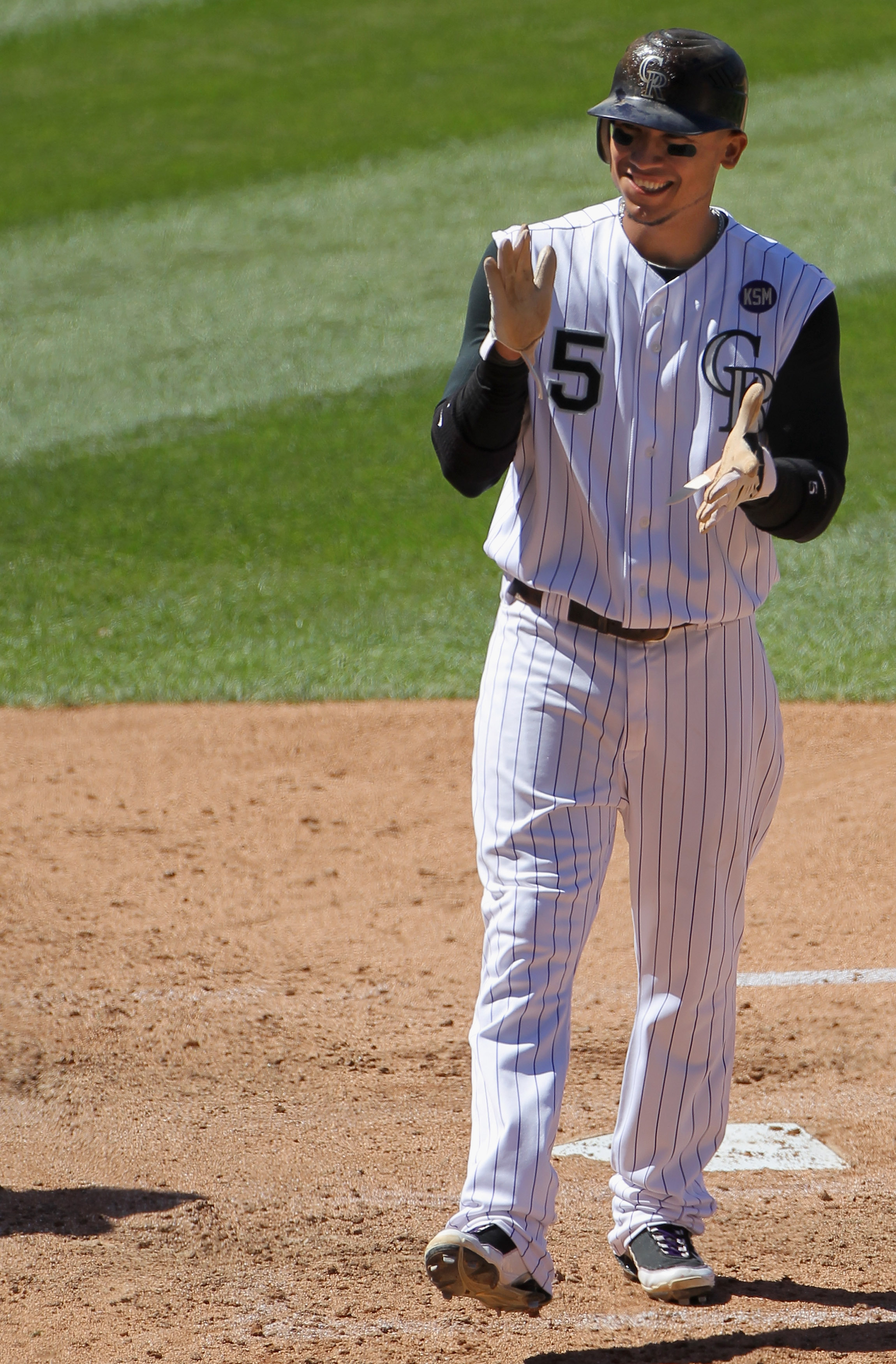 DENVER - SEPTEMBER 06:  Carlos Gonzalez #5 of the Colorado Rockies celebrates as he scores in the third inning against the Cincinnati Reds at Coors Field on September 6, 2010 in Denver, Colorado. The Rockies defeated the Reds 10-5.  (Photo by Doug Pensing