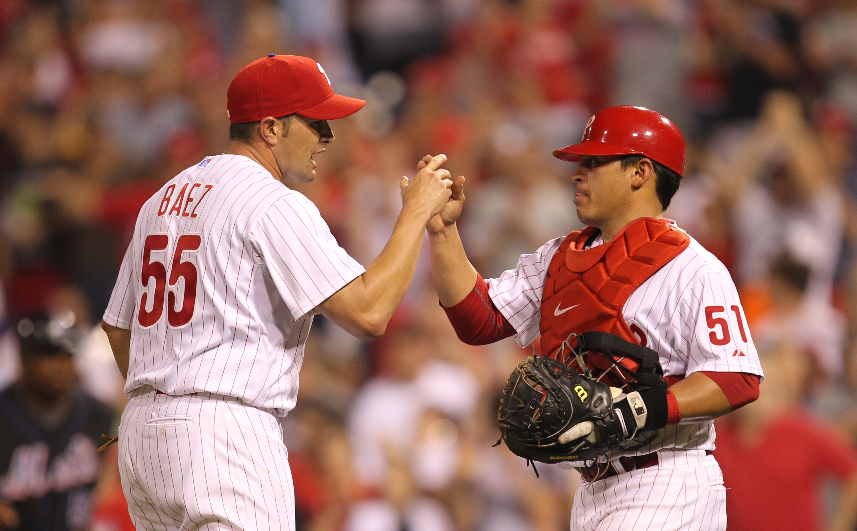 PHILADELPHIA - MAY 2: Relief pitcher Danys Baez #55 of the Philadelphia Phillies is congratulated by catcher Carlos Ruiz #51 after  a game against the New York Mets at Citizens Bank Park on May 2, 2010 in Philadelphia, Pennsylvania. The Phillies won 11-5.